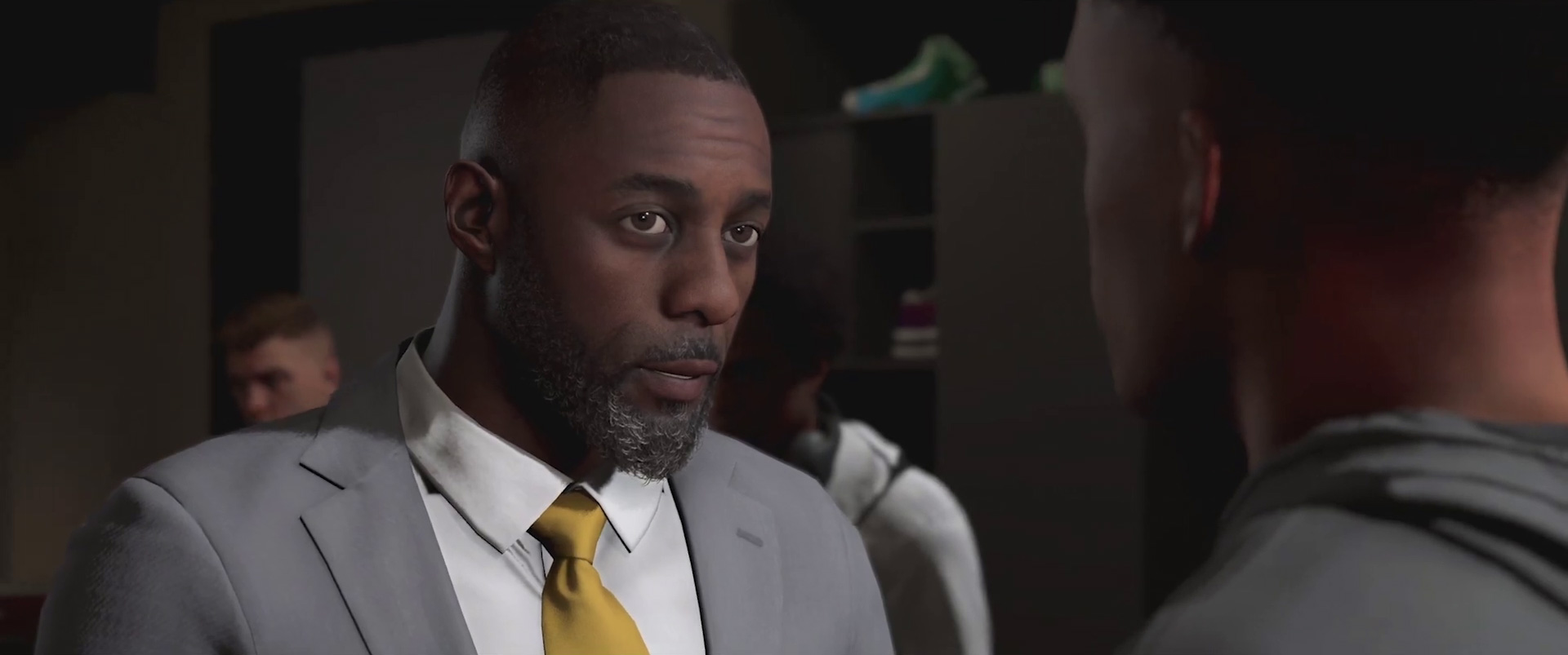 Idris Elba as a basketball coach wearing a light gray suit, white shirt, and mustard-yellow tie in NBA 2K20's MyCareer mode