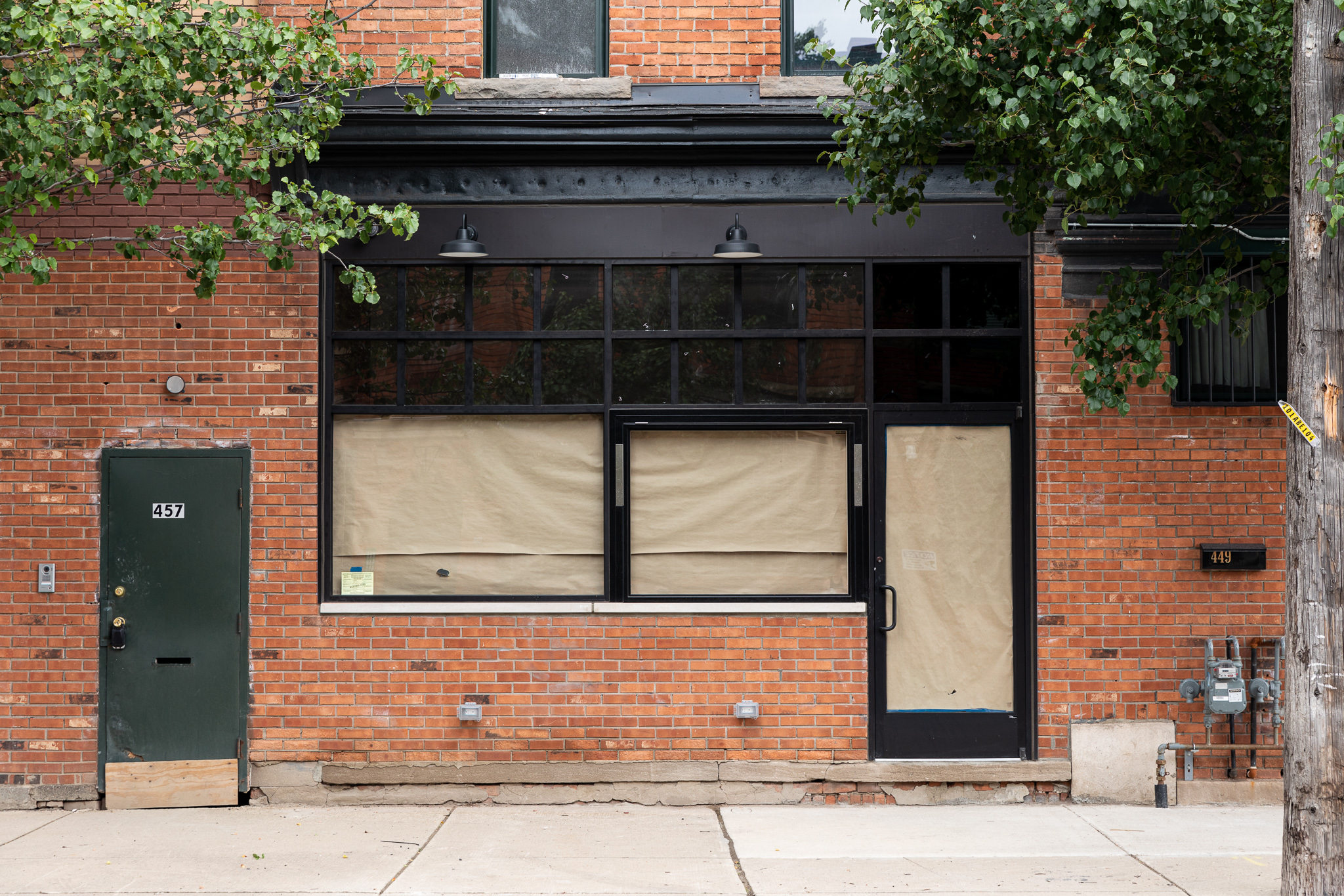 The building that houses Milwaukee Caffe has red brick walls and two sets of black-framed windows and a clear glass door. All the windows and doors are obscured by brown paper.