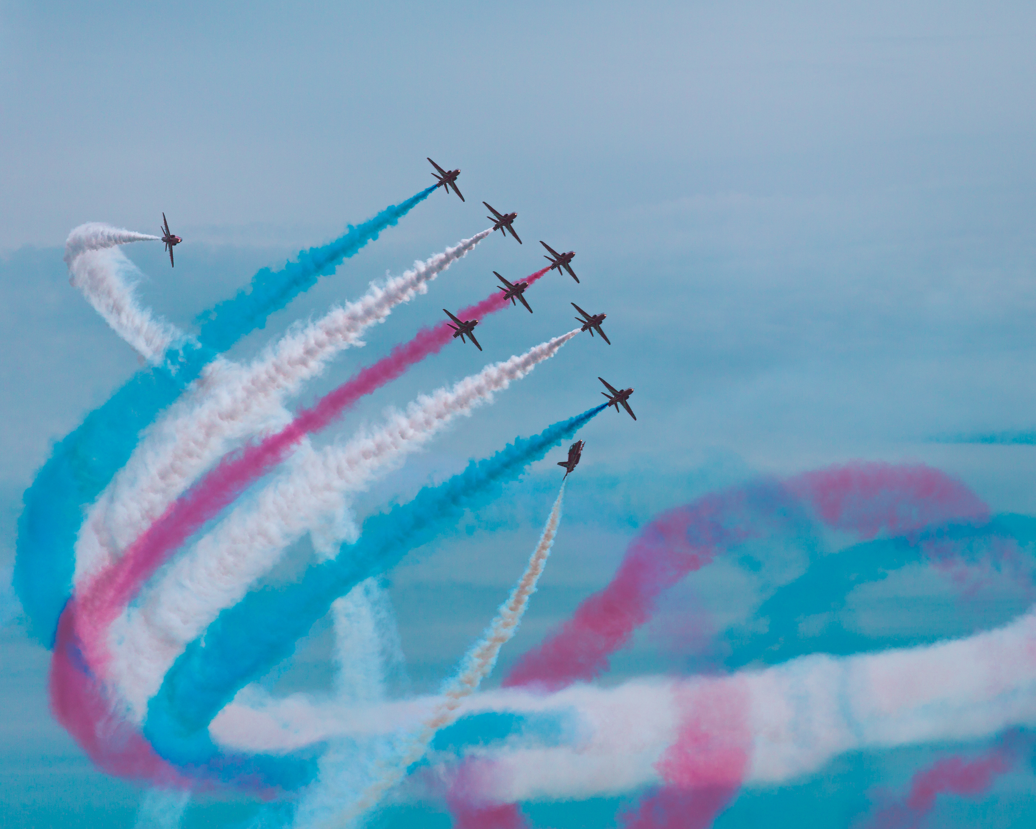 A formation of nine red jet fighters weave in and out, leaving behind an intertwined pattern of red, white, and blue smoke trails.