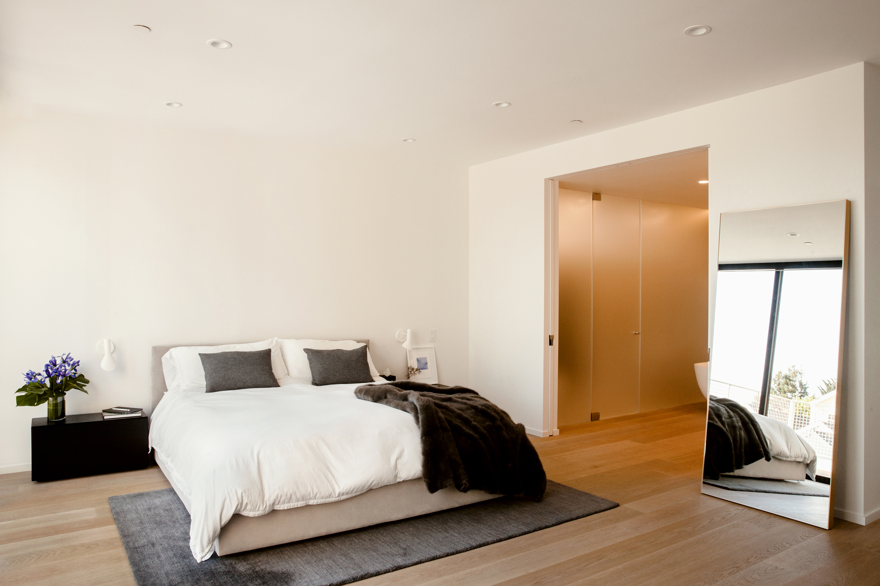 A white bedroom with a beige bed on gray rug, large rectangular mirror leaning against a wall and a view into the master bath.