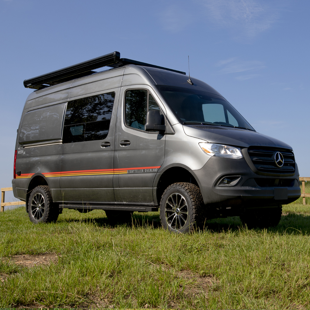 A gray Mercedes Sprinter van with a yellow and red stripe sits on the grass.