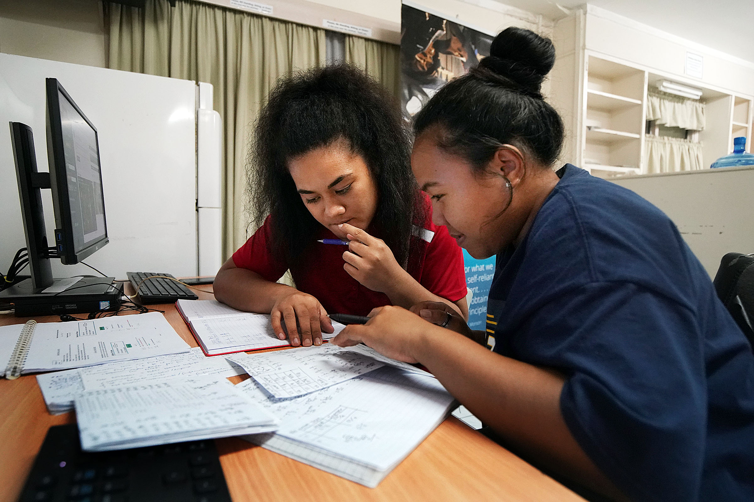 Clorissa Tauti, left, and Shirley Sa'u work together to learn personal finance during a group session of the PathwayConnect program in Apia, Samoa, on Thursday, May 16, 2019.