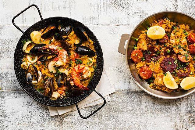 Two bowls of paella on a white table.