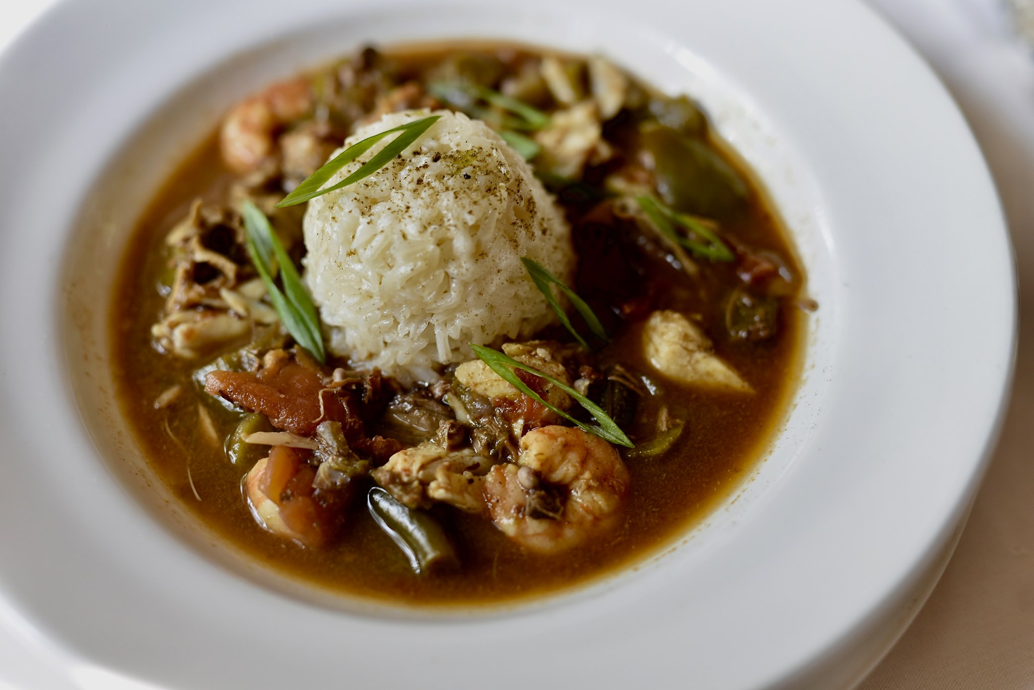 A white bowl of dark roux gumbo with a scoop of white rice in the center