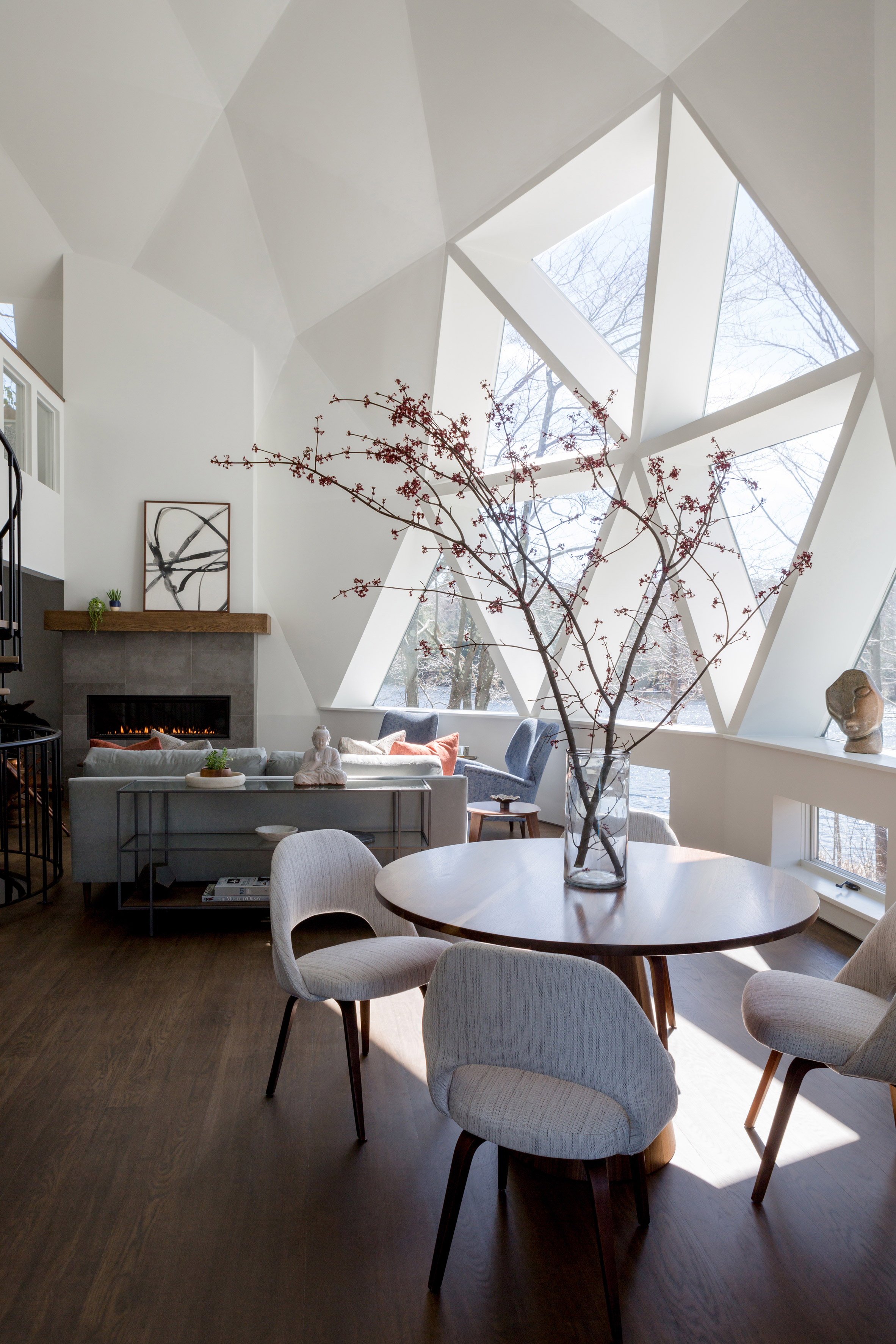 Domed living room with a gray sofa, fireplace, and round dining table with chairs, in front of triangular windows.