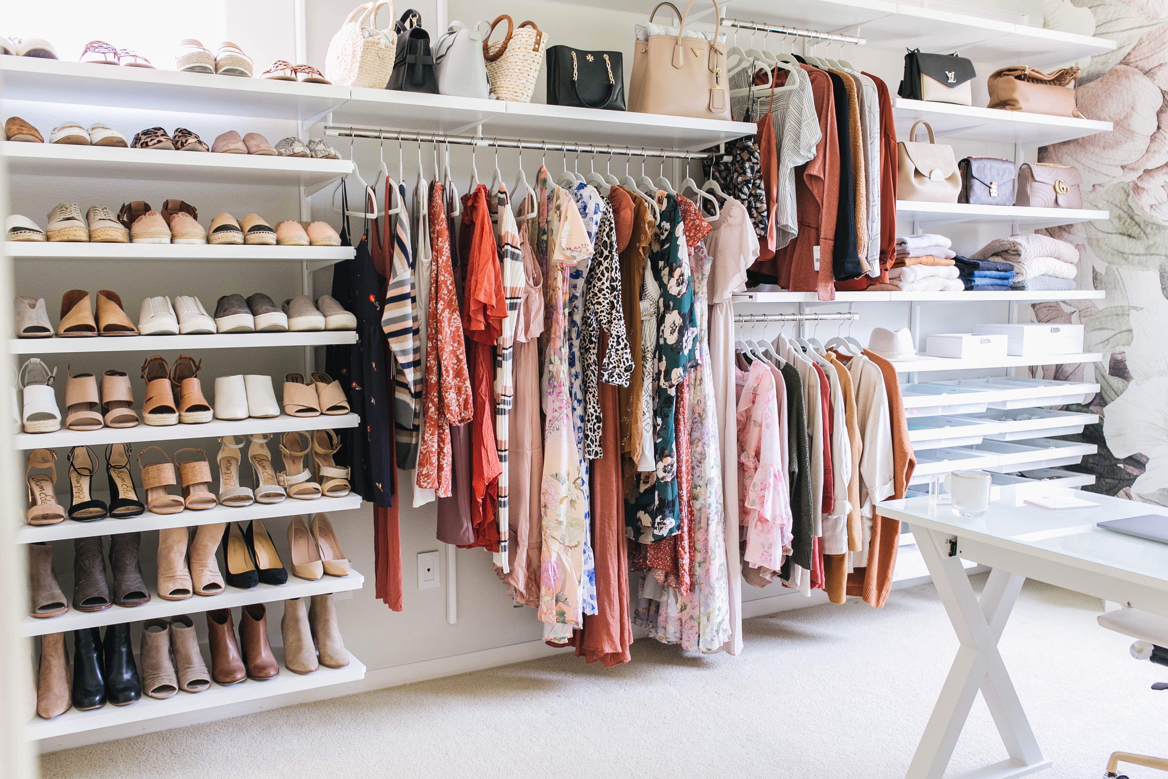 A custom closet features white shelves of shoes and hanging clothes from the Container Store.