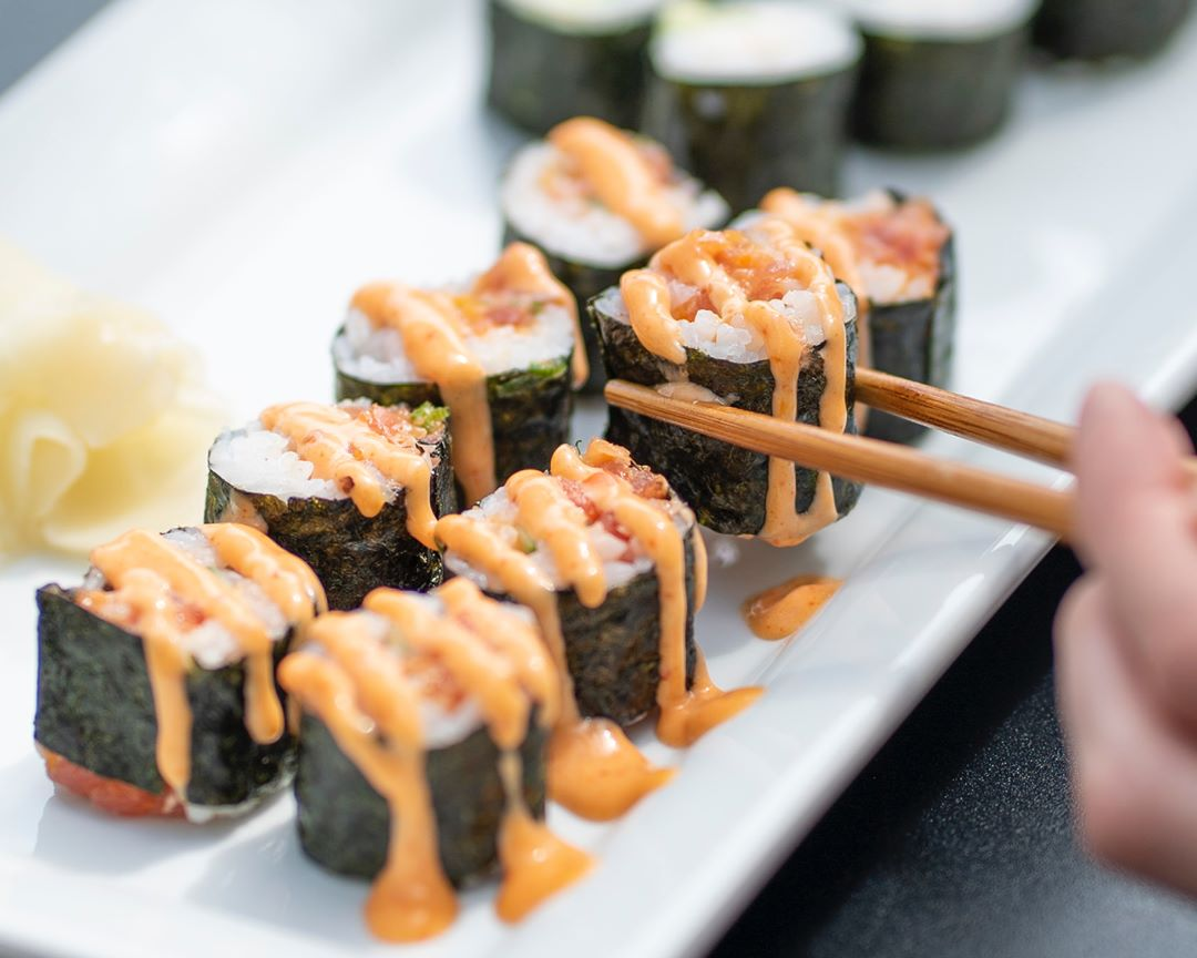 A sushi roll, drizzled in sauce, being picked up with chopsticks.