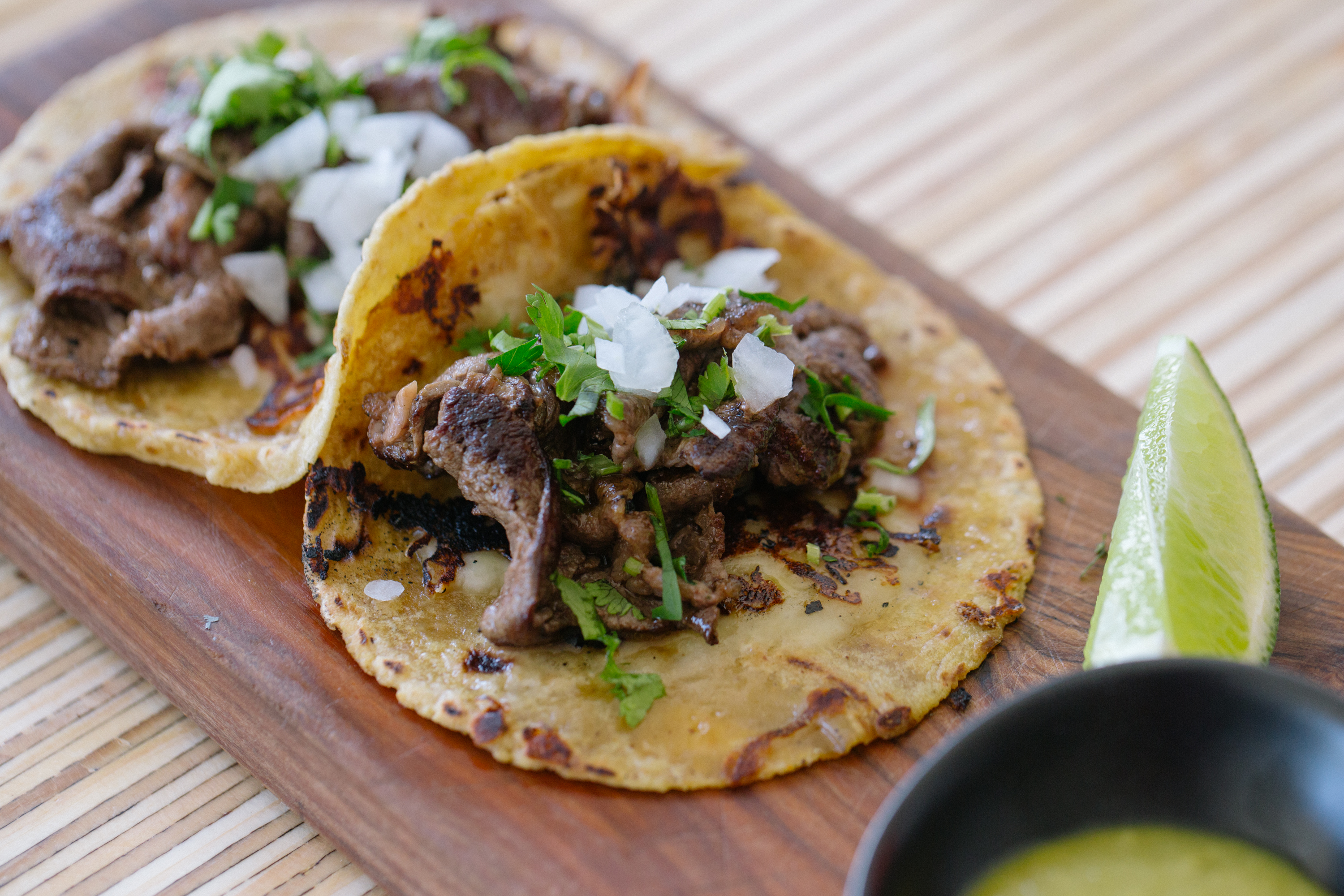 Two tacos with beef and onions sit on a wooden board