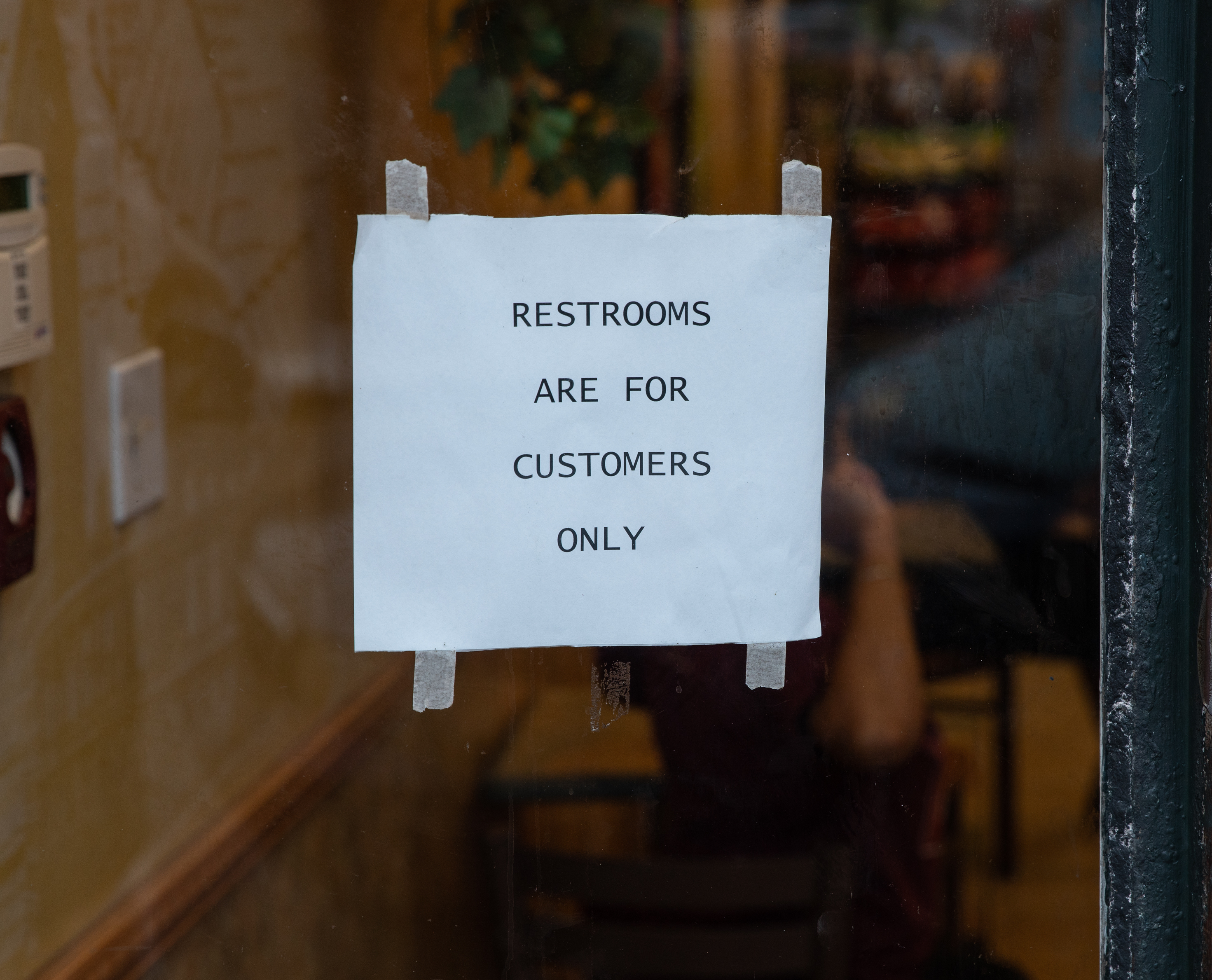 "A paper sign taped to a window that reads ""Restrooms are for customers only""."