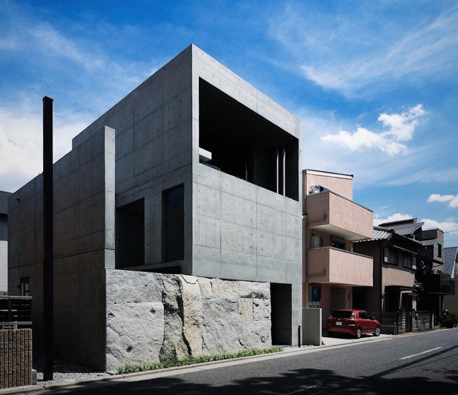 Boxy concrete house rests on stone base.
