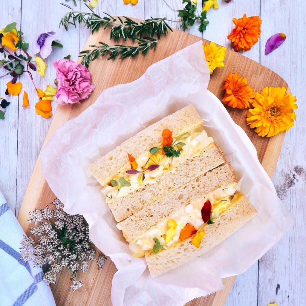 An egg salad sandwich with the crusts cut off and edible flowers at the new Bread n' Chu