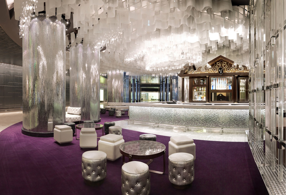 The violet carpeting, low, cream-colored seating seating and pearl white bar top at the Vesper Bar,