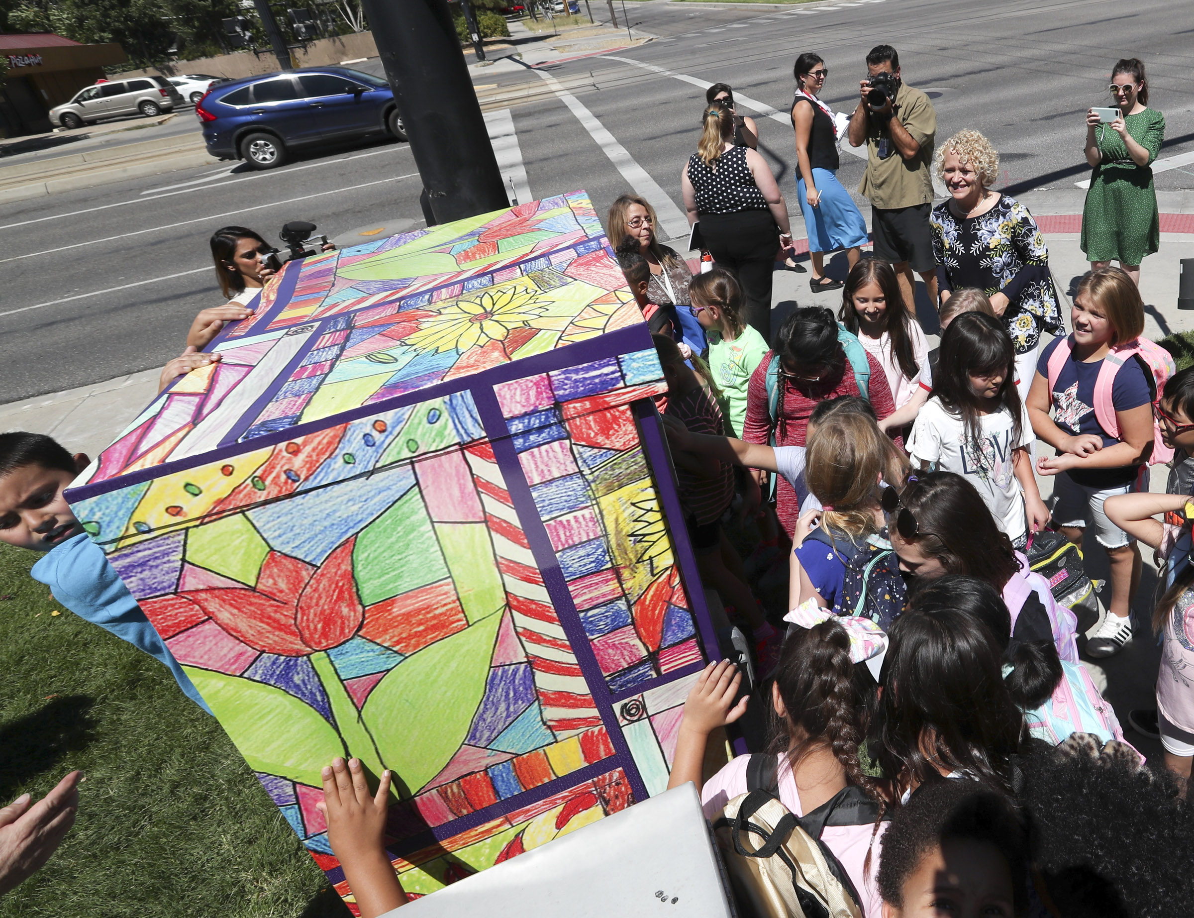 Salt Lake City Mayor Jackie Biskupski and Bennion Elementary School students check out a utility box covered with the students' art after it was unveiled in Salt Lake City on Tuesday, Aug. 20, 2019. The ColorSLC project aims transform city utility boxes, like the one across the street from the school at 429 S. 800 East, into public art. Through the ColorSLC program, 28 utility boxes have been wrapped with more than 1,100 of pieces of original art created by students at each of the 28 elementary schools in the Salt Lake City School District. It is the city's largest public art installation.