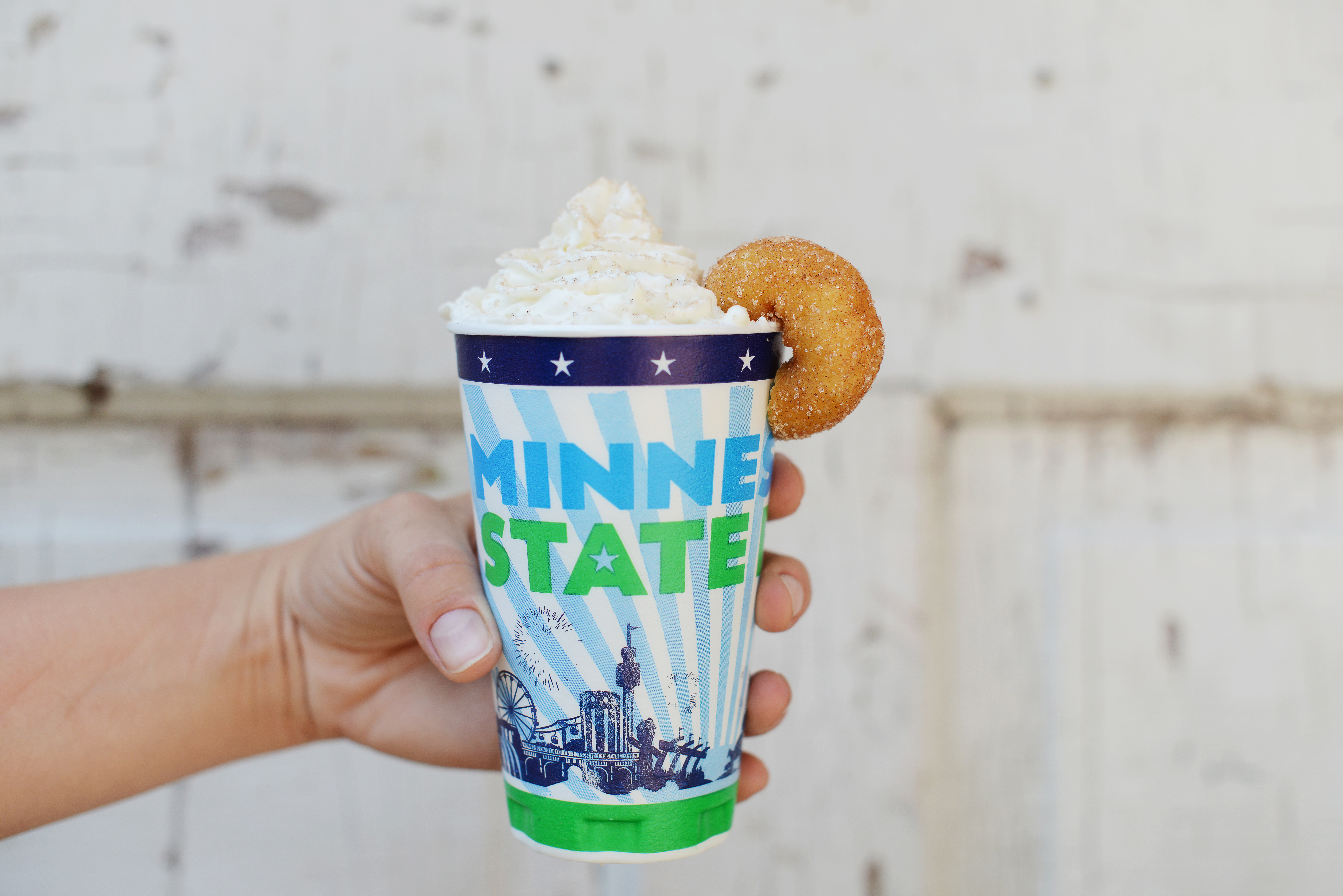 A Minnesota State Fair official cup topped with whipped cream and a mini doughnut hanging off the edge