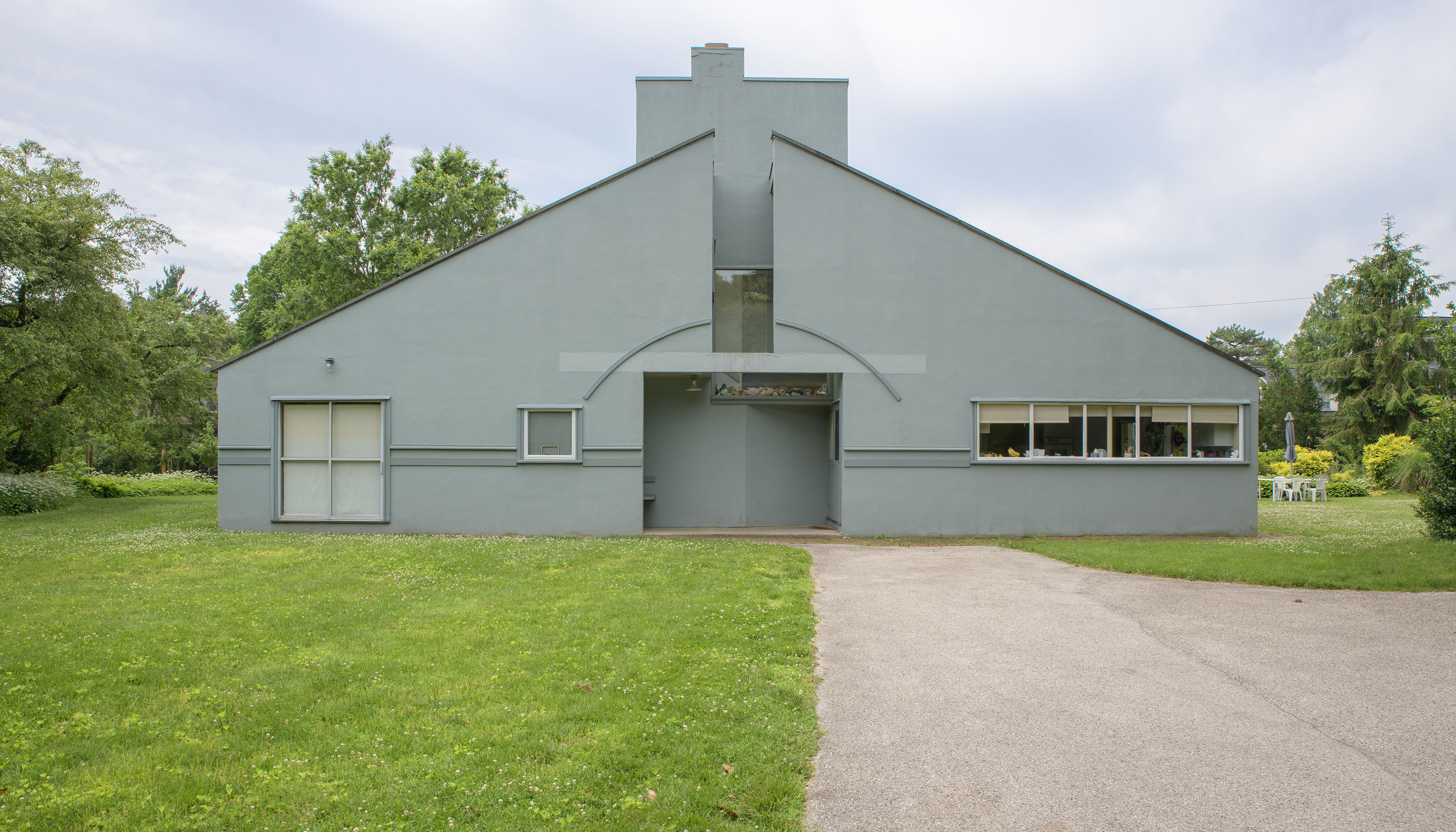 The Vanna Venturi house in Philadelphia. The exterior of the house is light blue with a sloped roof and large entrance. There is a path leading up to the entrance. There is a large green grass lawn adjacent to the path in front of the house.