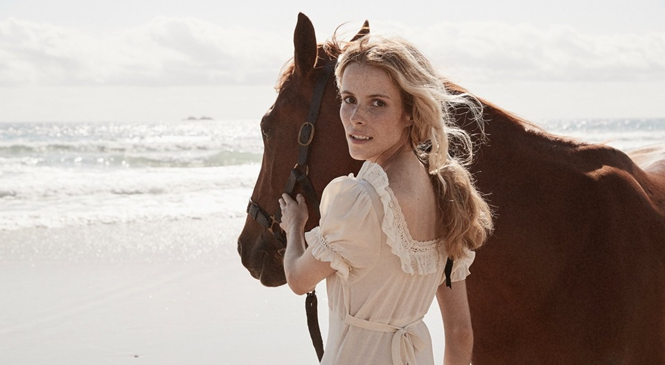 A woman in a puff-sleeve dress and a horse stand by the ocean.