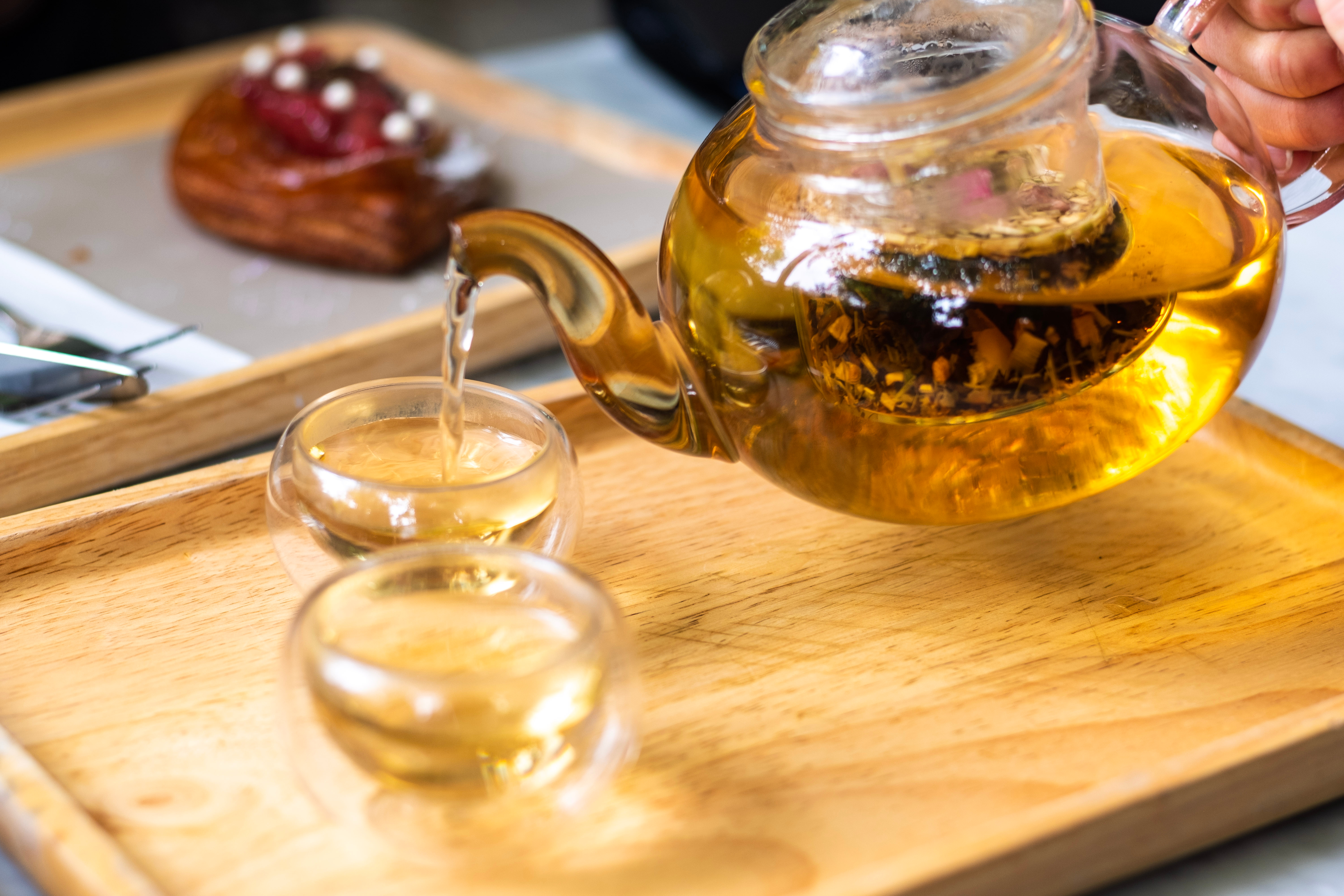 A clear glass teapot with loose tea in a strainer pours tea into two clear glass cups on a wooden tray.