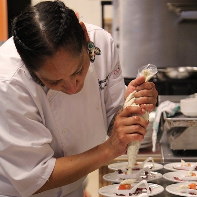 Norma Condo, in a chef's uniform, squeezes a piping bag.