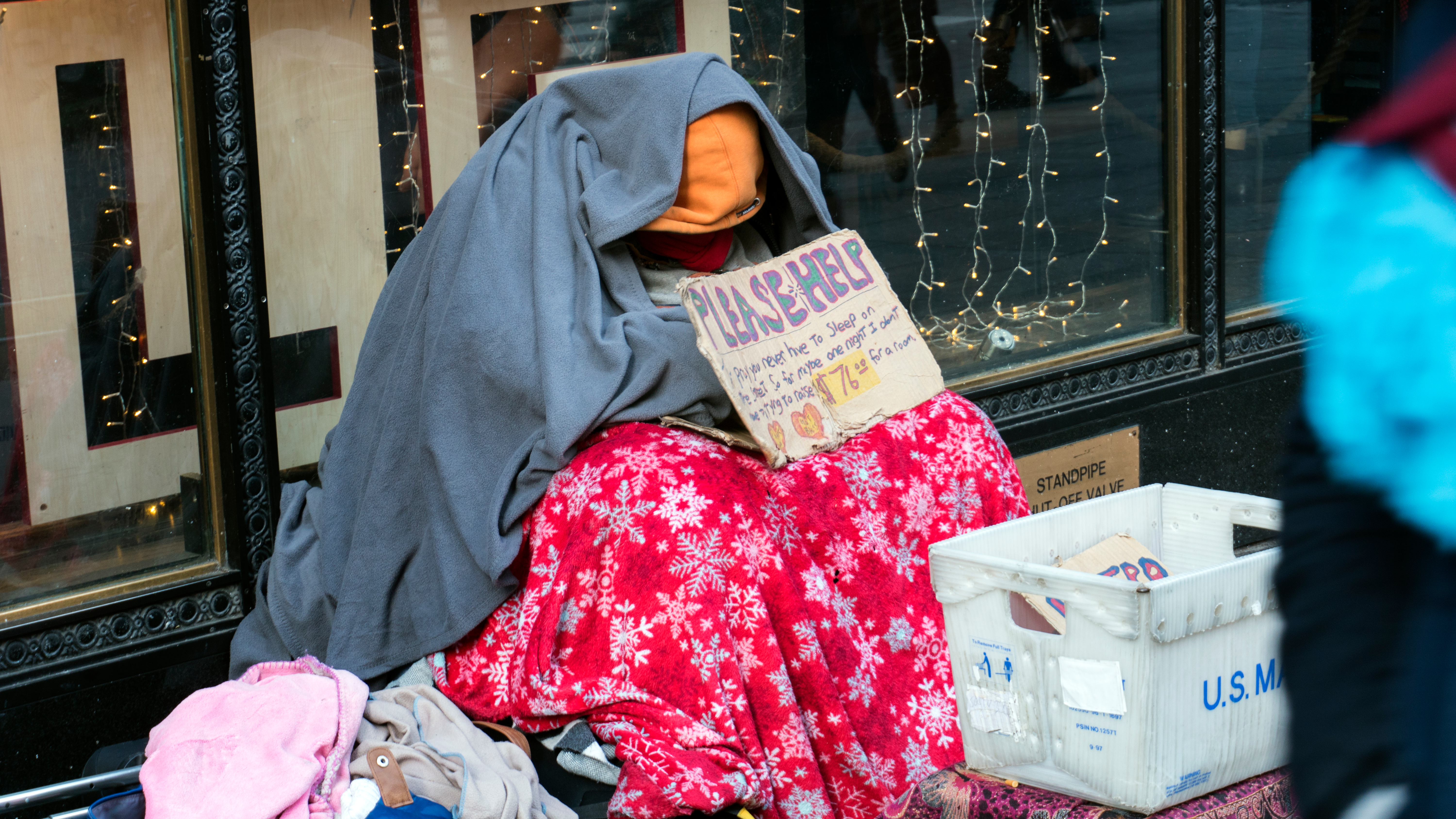 """A homeless person sitting in a New York City street, covered in blankets with a sign that says """"Please Help."""""""