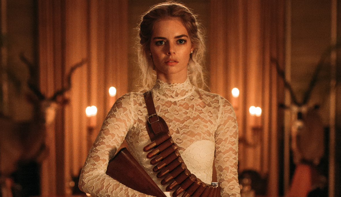 Samara Weaving holds a gun, wearing a wedding dress, in the movie Ready or Not.
