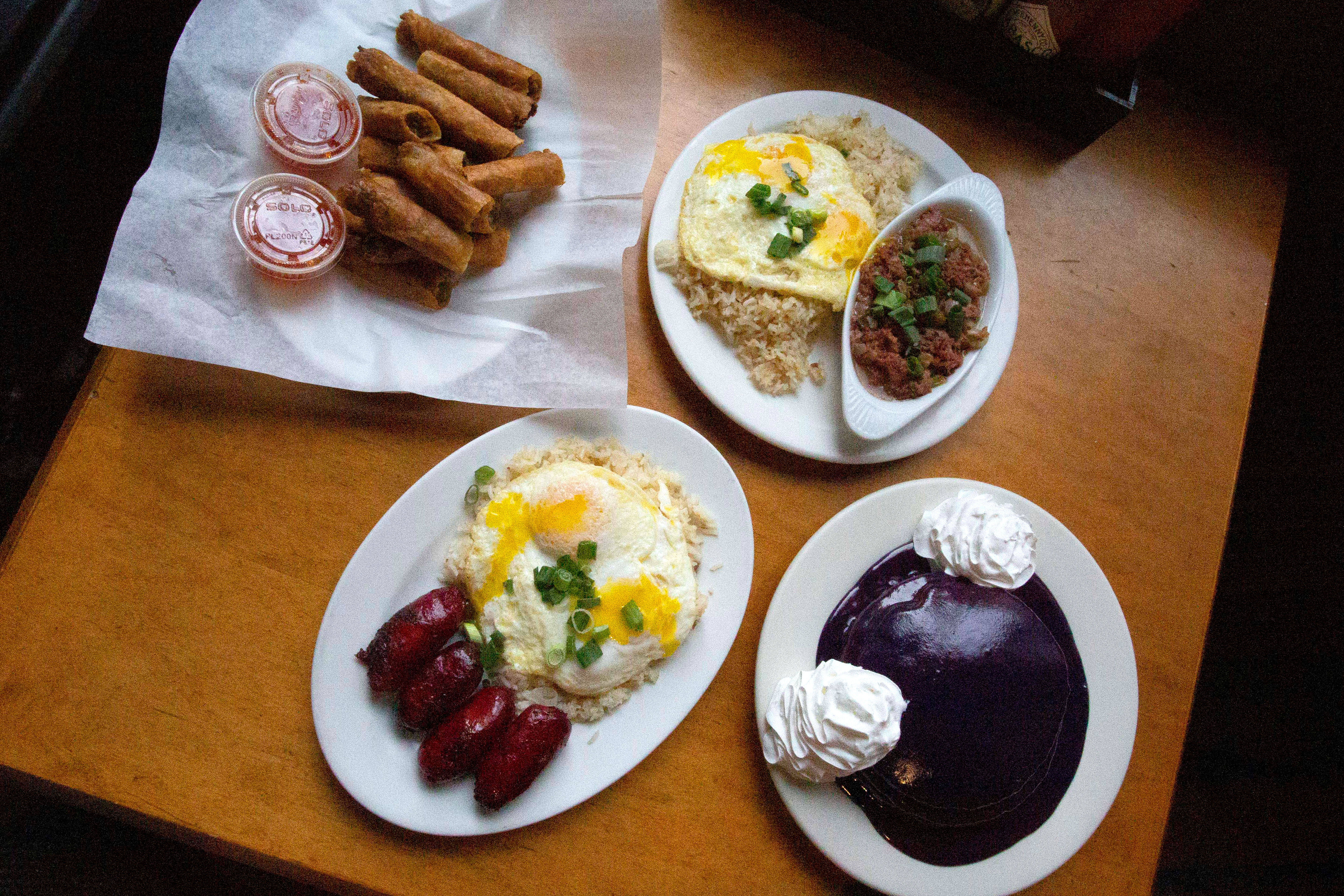 A bird's eye view of various Filipino breakfast dishes at Ludi's Restaurant and Lounge, including ube pancakes and corned beef silog.