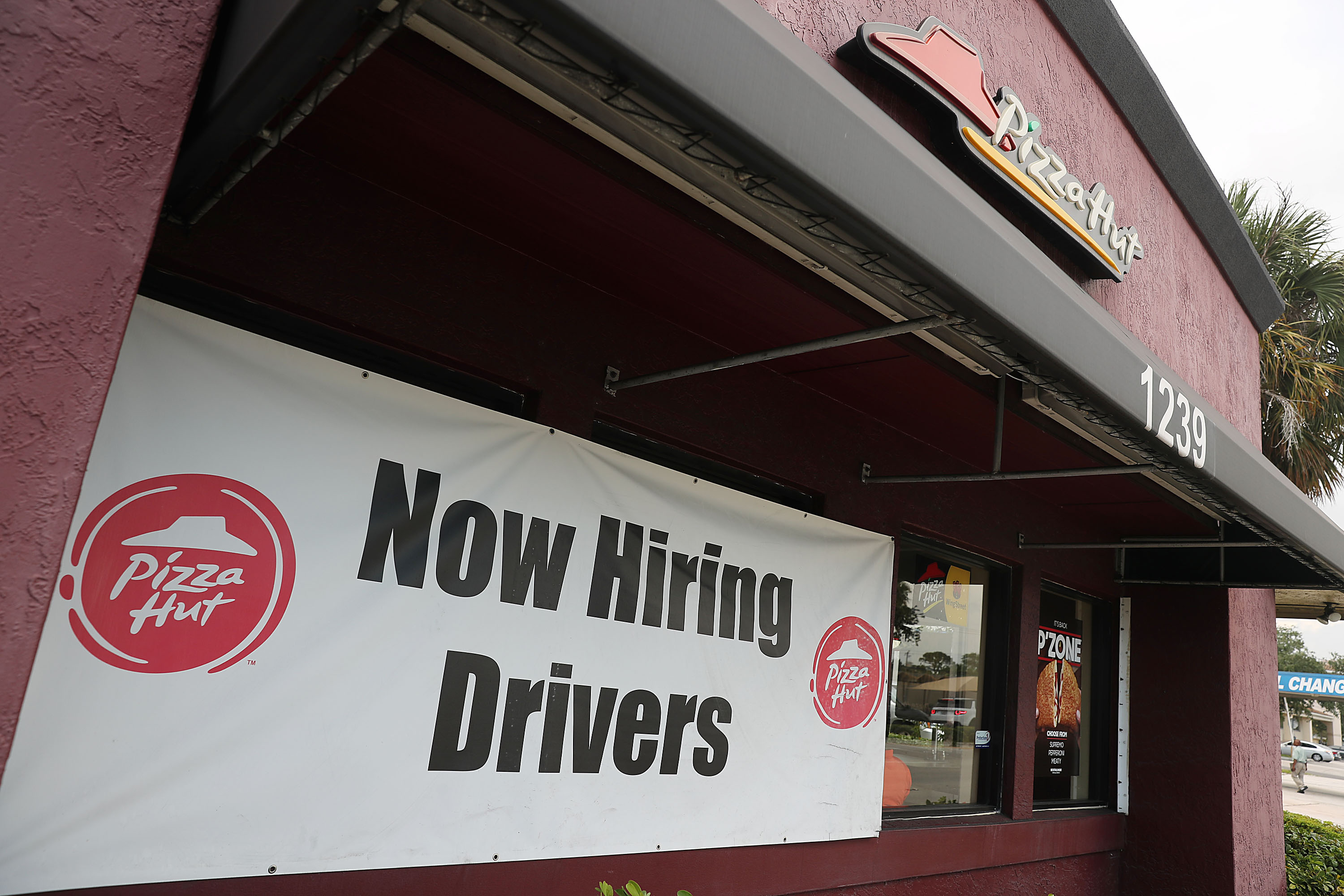 "A banner sign outside a Pizza Hut restaurant reads ""Now hiring drivers."""
