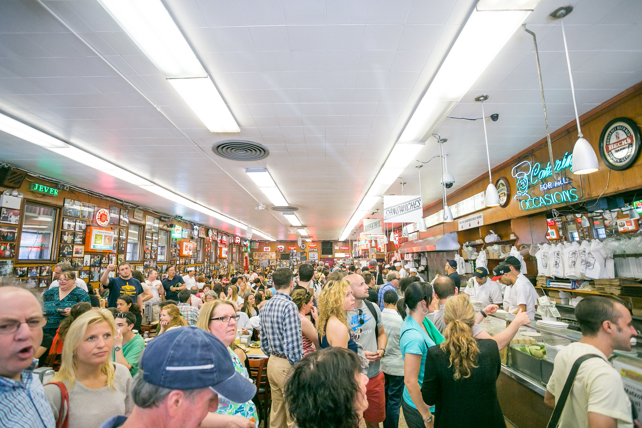 A large crowd gathers inside the bright Katz's Deli in New York City.