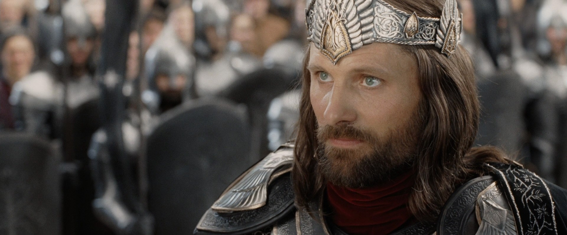 Aragorn from Lord of the Rings looks up, wearing a crown. His hair looks soft and he is well-groomed: it's his coronation.