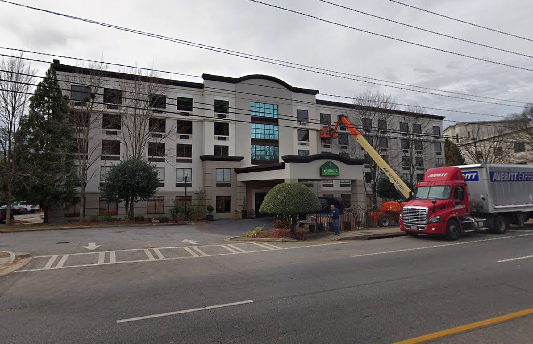 A stucco-faced, five-story hotel in Buckhead is undergoing renovations, with a cherry-picker and moving truck out front.
