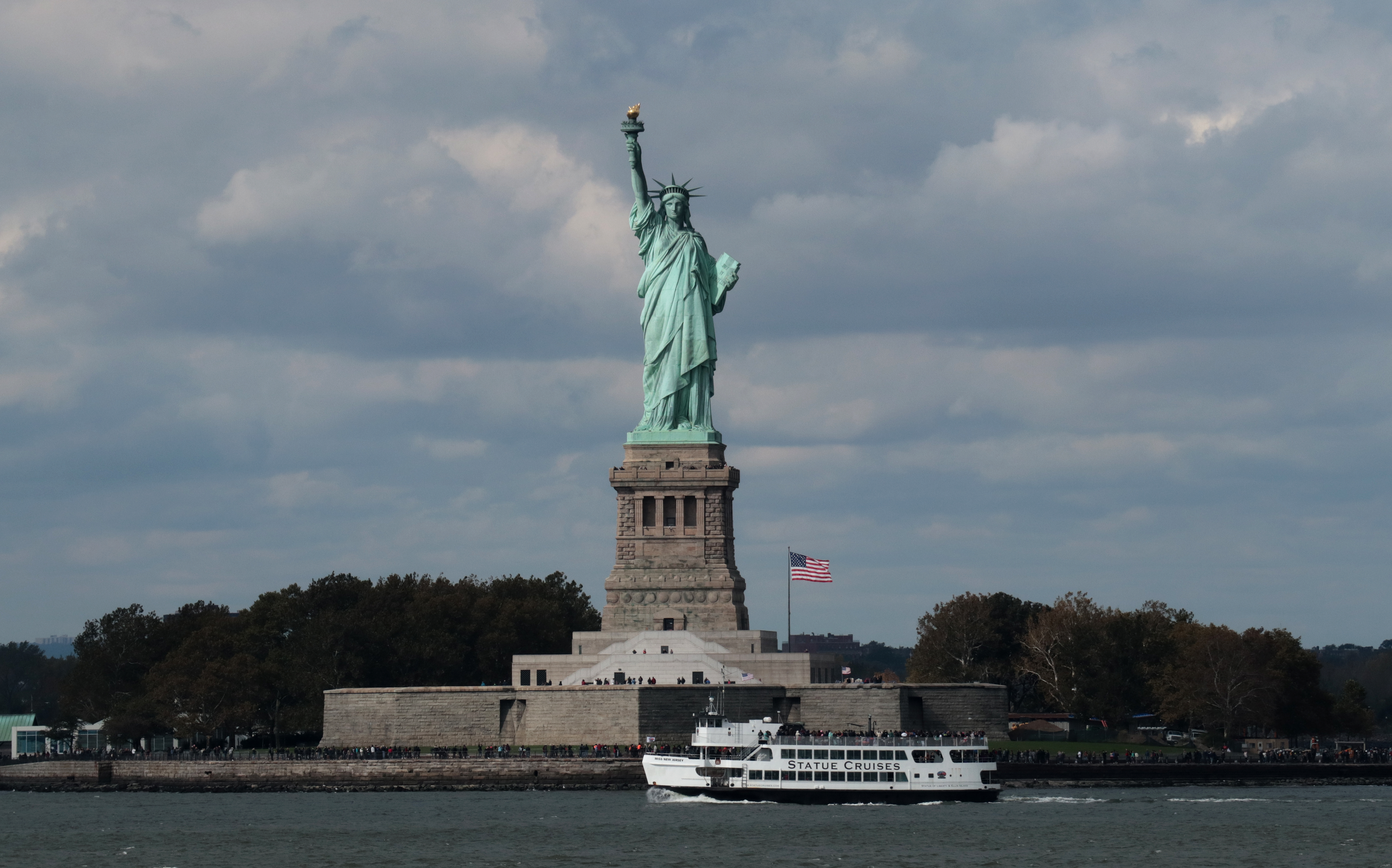 A ferry boat passes by the Statue of Liberty in New York Harbor.