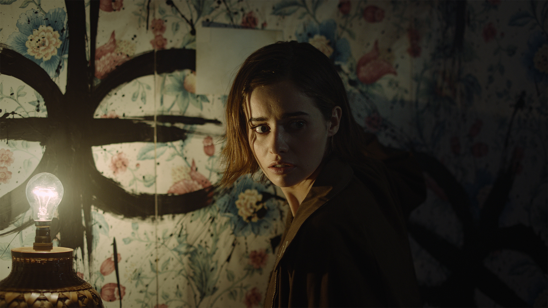 Erica, a white woman with dark hair, stands in a dimly lit room. She is looking over her shoulder with a concerned expression. A symbol has been painted on the wall.
