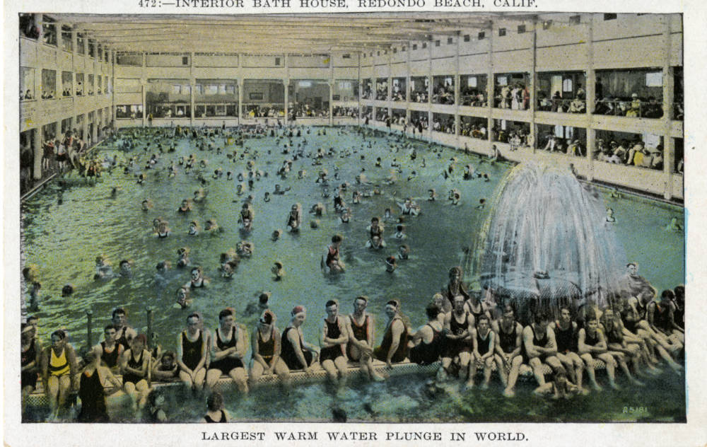 A close-up of a colored vintage postcard showing young men and women crowded inside a massive swimming pool in the Redondo Beach Bath House. There's a large fountain in the forefront and the pool is rimmed in observation areas.