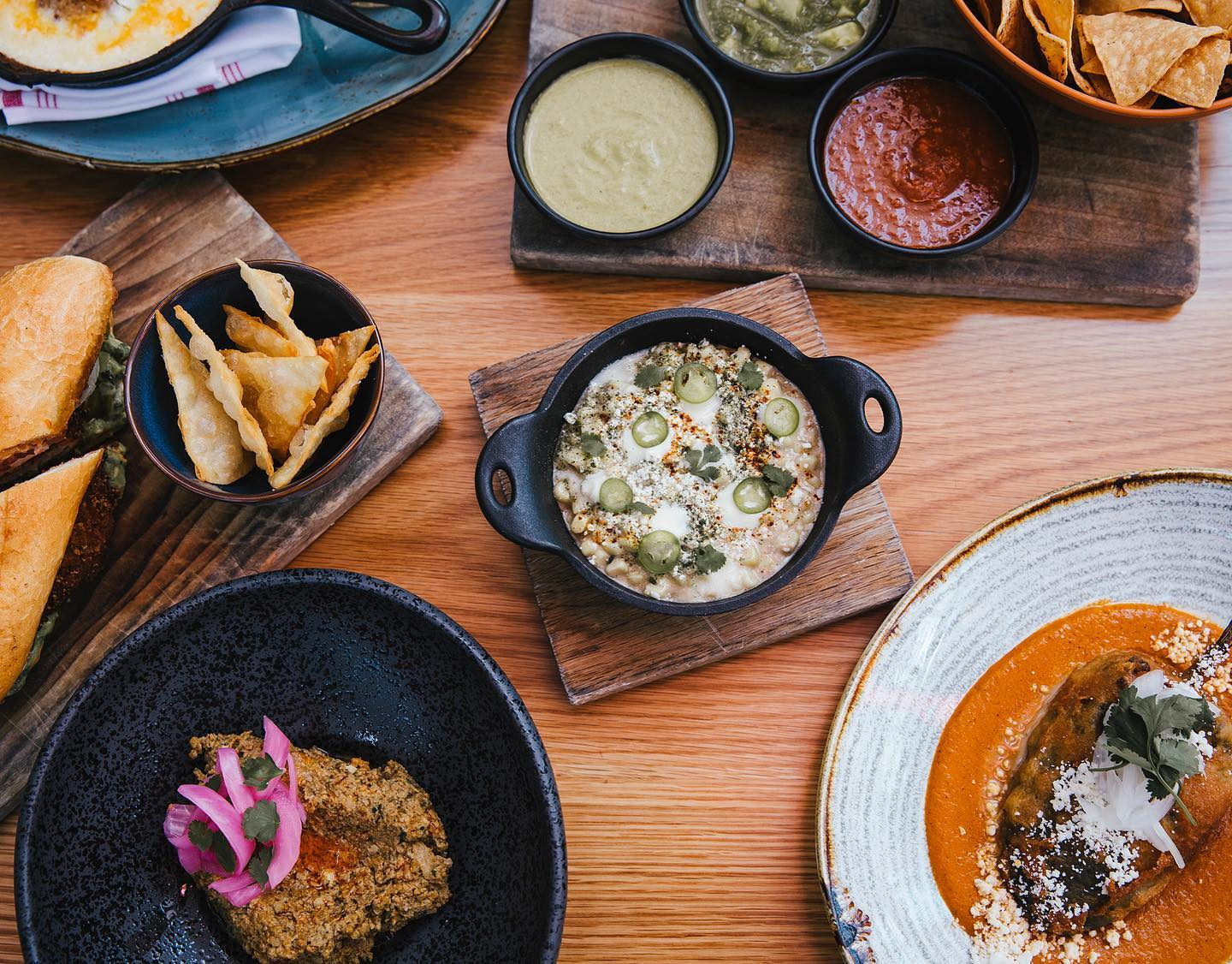 Esquites, chile relleno, sikil pak, and other Mexican dishes on a table