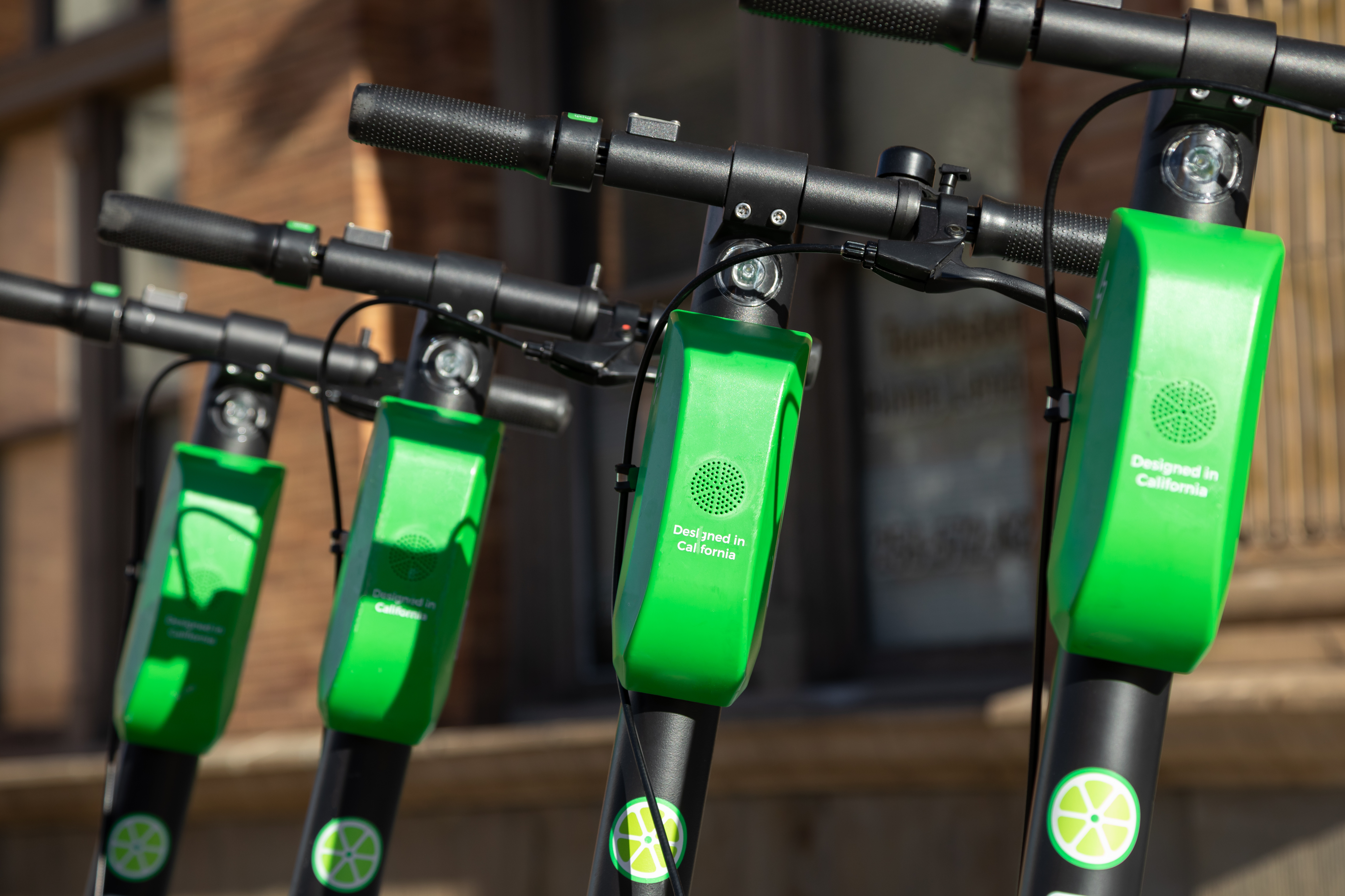 Four sets of handlebars, each with a rectangular green battery pack attached and a round lime logo at the base, with bricks in the background.