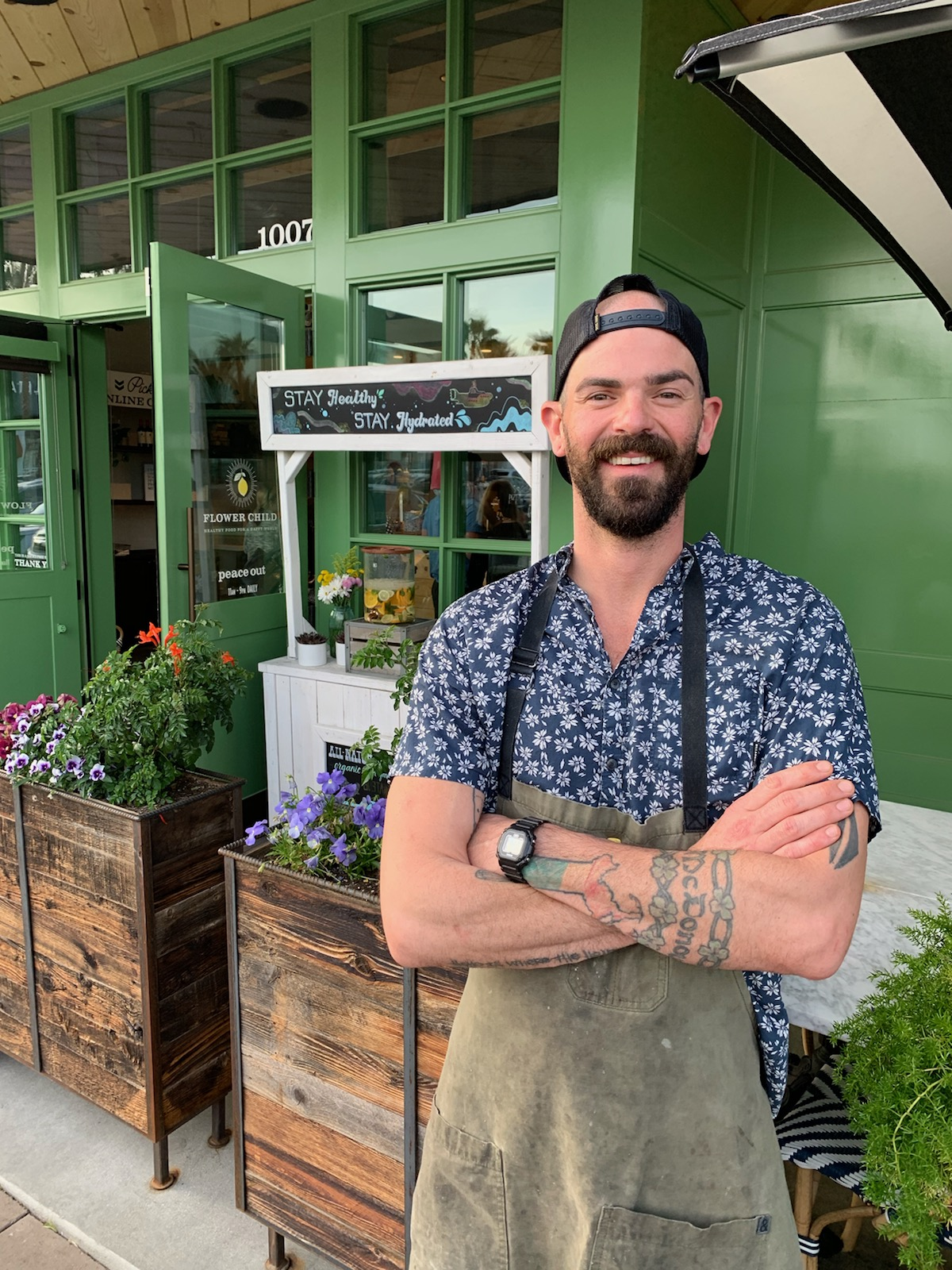 A chef in a print shirt cross his arms