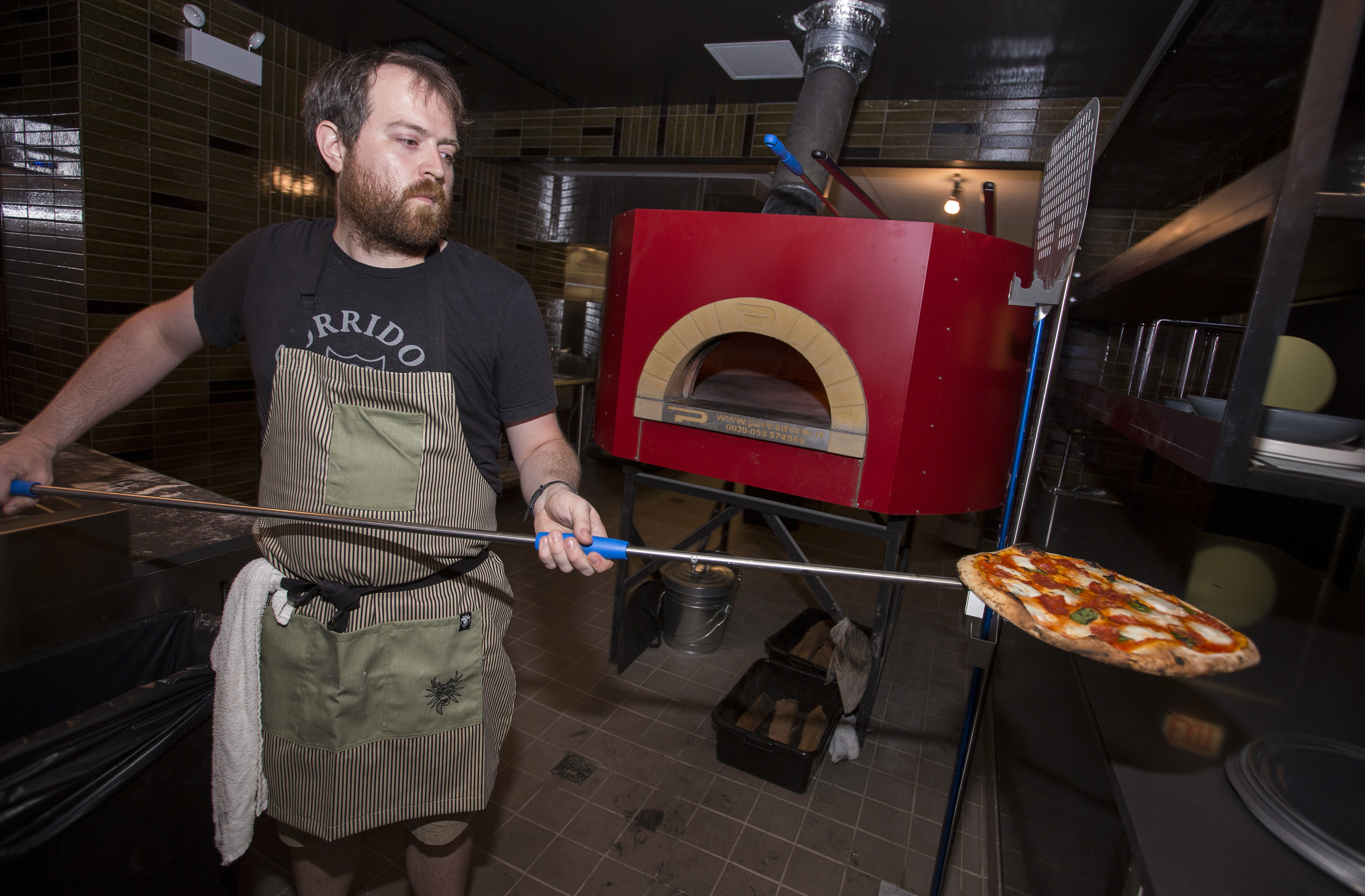 Man taking a thin-crust pizza out of an oven.