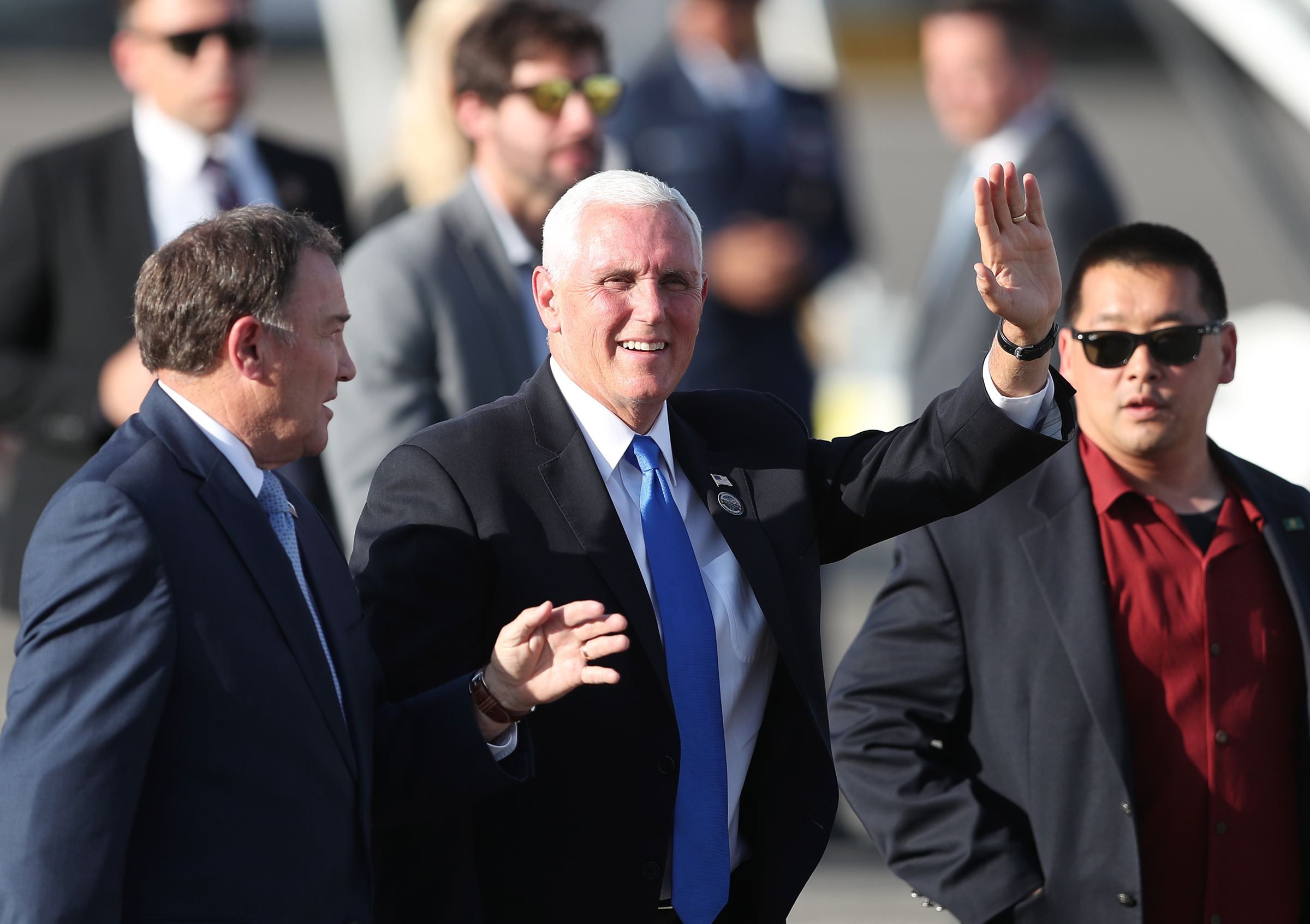 Vice President Mike Pence waves as he and Gov. Gary Herbert greet the crowd at the general aviation facilities at Salt Lake City International Airport on Wednesday, Aug. 21, 2019.