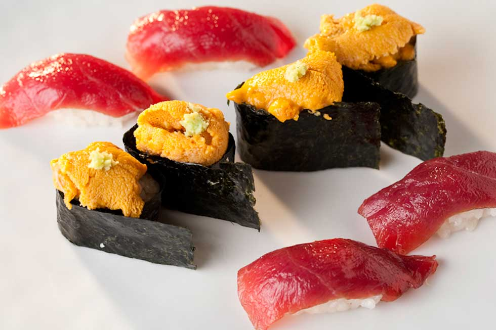 Four pieces of sushi topped with uni surrounded by four tuna nigiri.