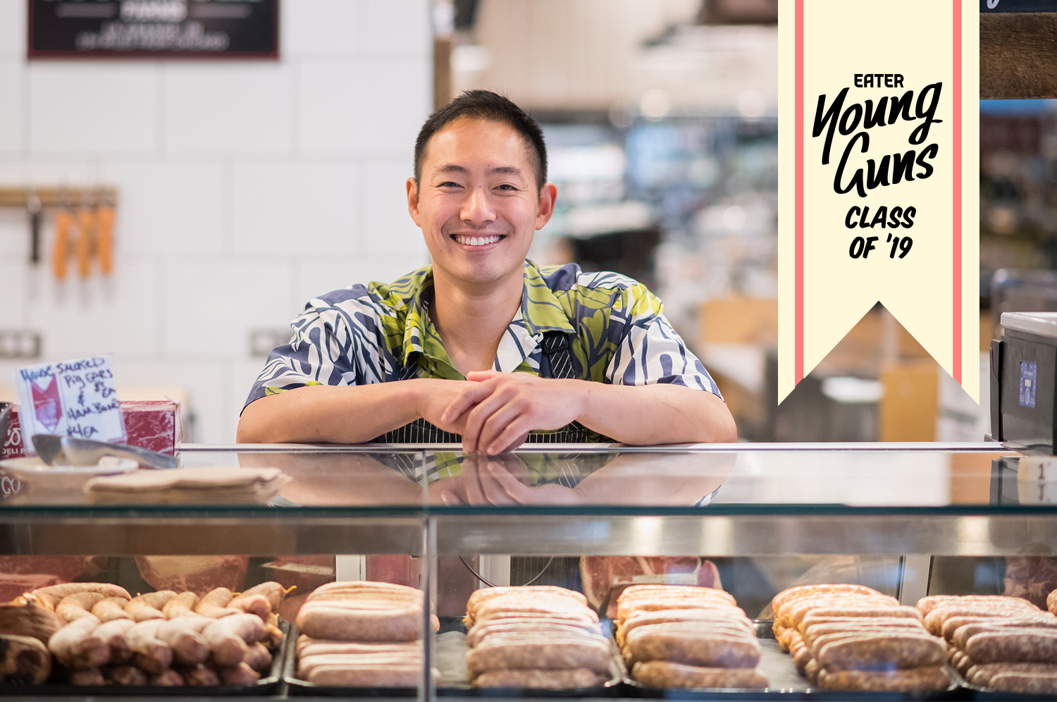 Jason Chow smiles while standing behind a butcher counter.