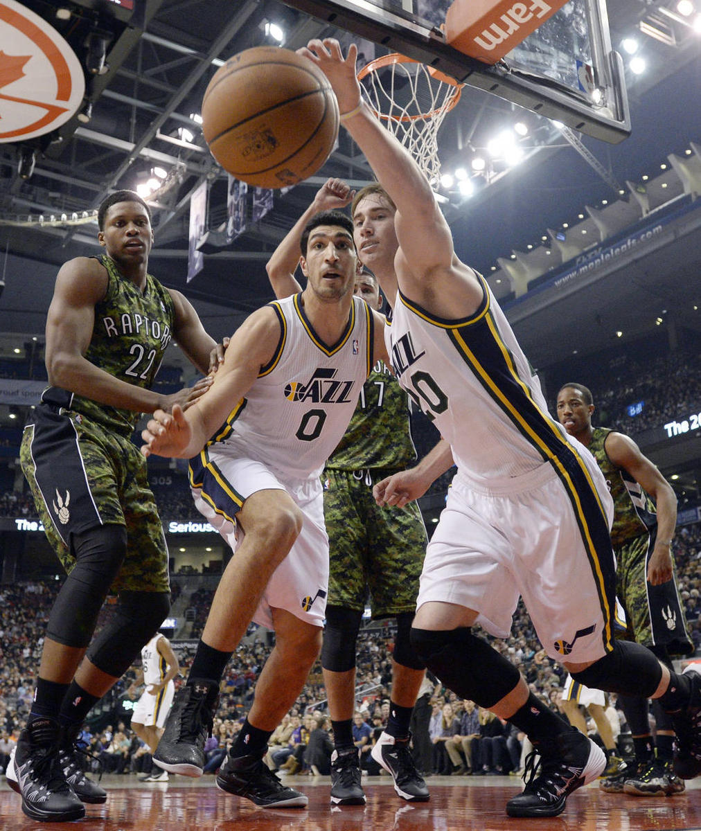 Utah Jazz center Enes Kanter (0) and teammate Gordon Hayward, right, battle Toronto Raptors' Rudy Gay for the ball during the first half of an NBA basketball game in Toronto on Saturday, Nov. 9, 2013.