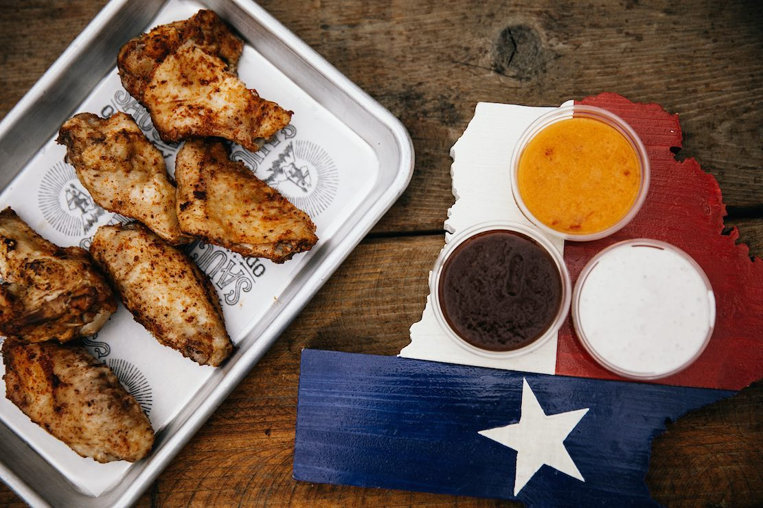 A tray of chicken wings next to a wooden tray painted to look like the Texas flag with three sauces in round containers