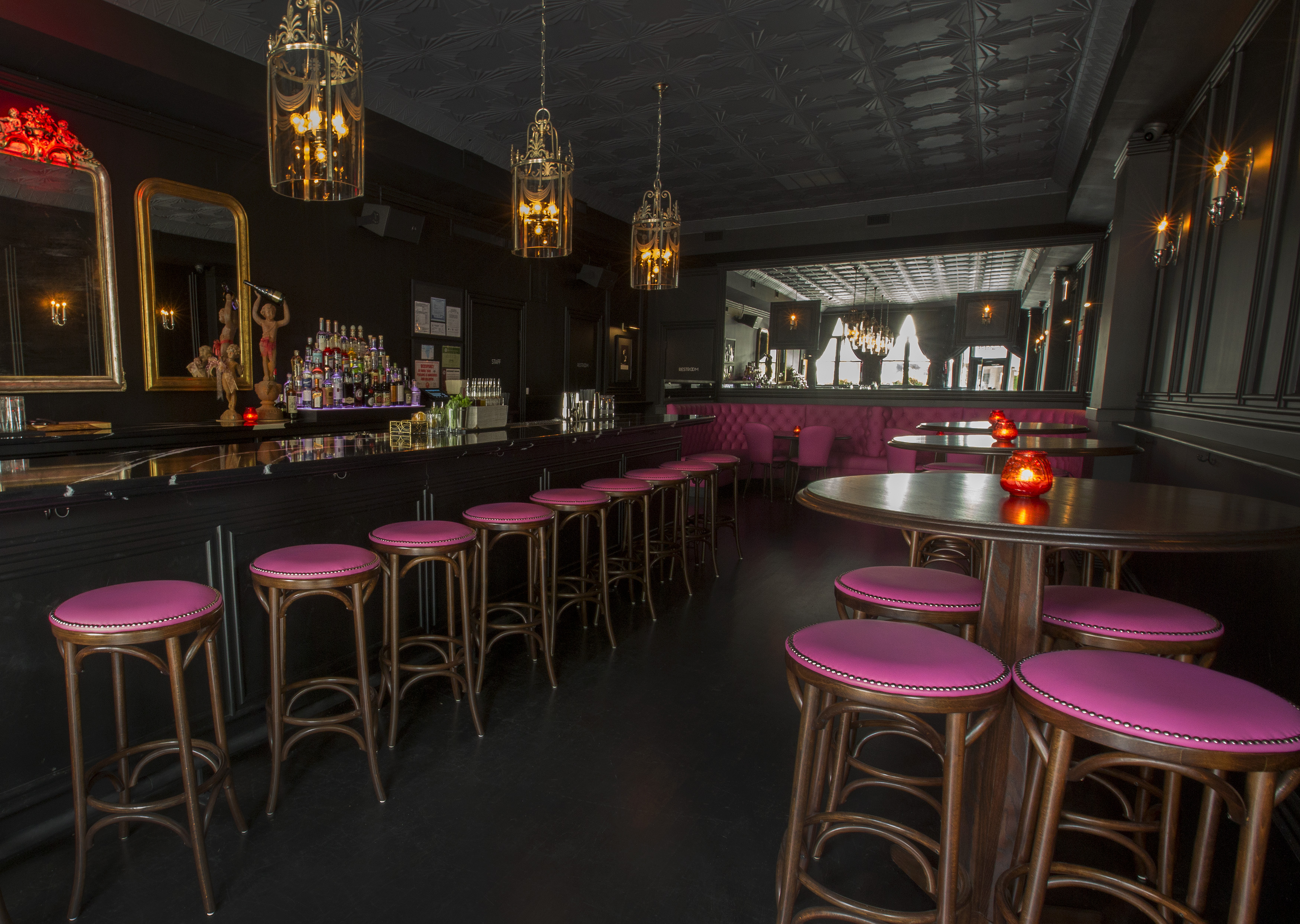 A bar with black walls, vintage gold mirrors and light fixtures, plus pink stools.