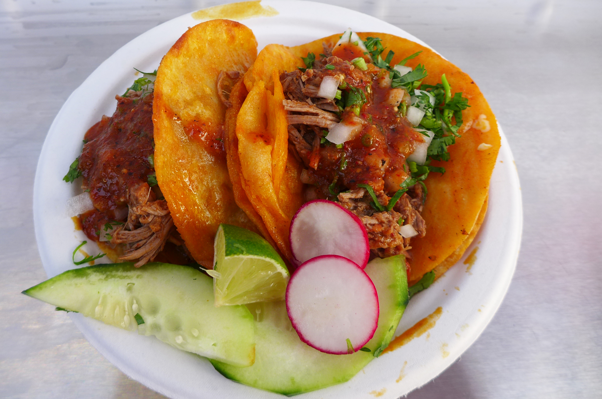 A pair of tacos stuffed with meat, green cilantro, and onions, served with sliced radishes and cucumbers