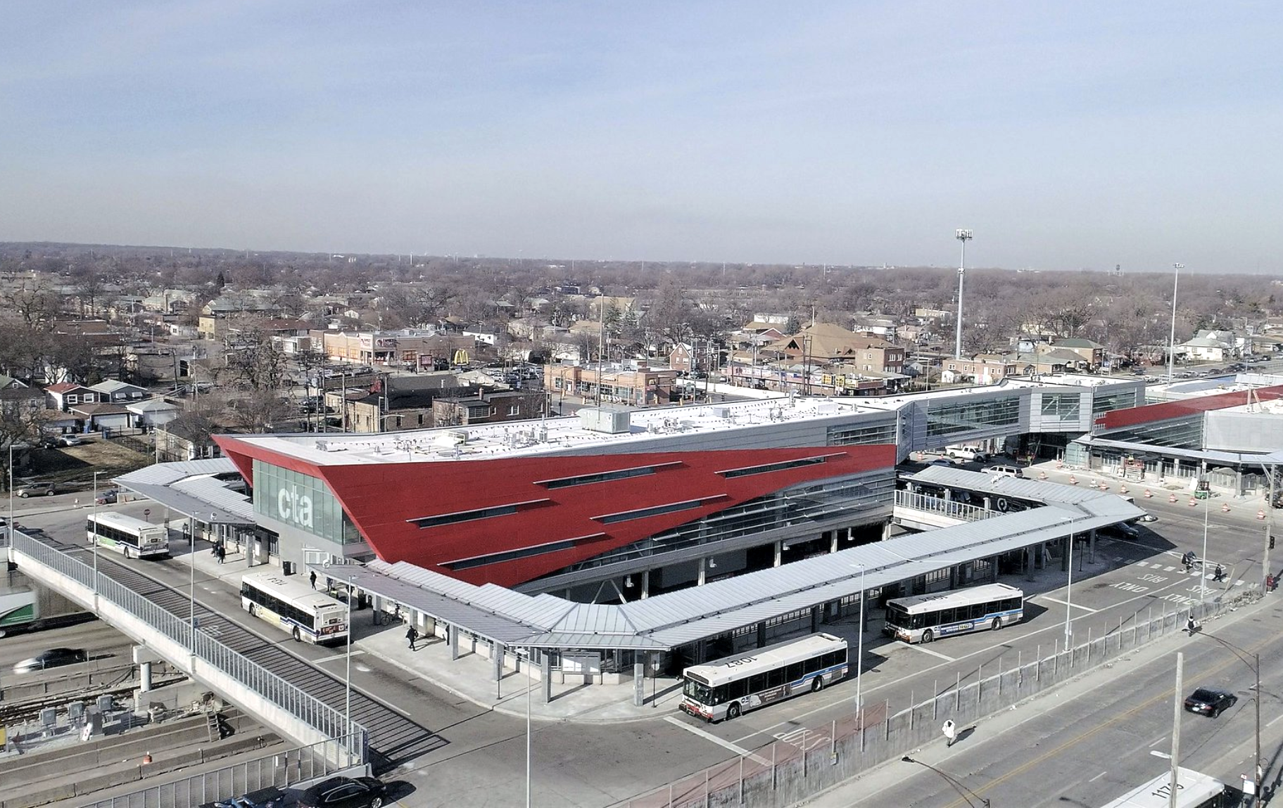 "An aerial view of a train and bus terminal with thin slit windows on a red and white sheet metal shelter with ""CTA"" printed on the glass frontage."