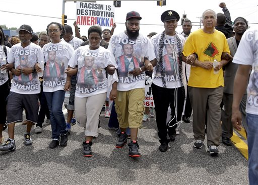 Michael Brown Sr. (center) leads a march in remembrance of his son, Michael Brown on Sunday, Aug. 9, 2015, in Ferguson, Missouri. | Jeff Roberson/AP