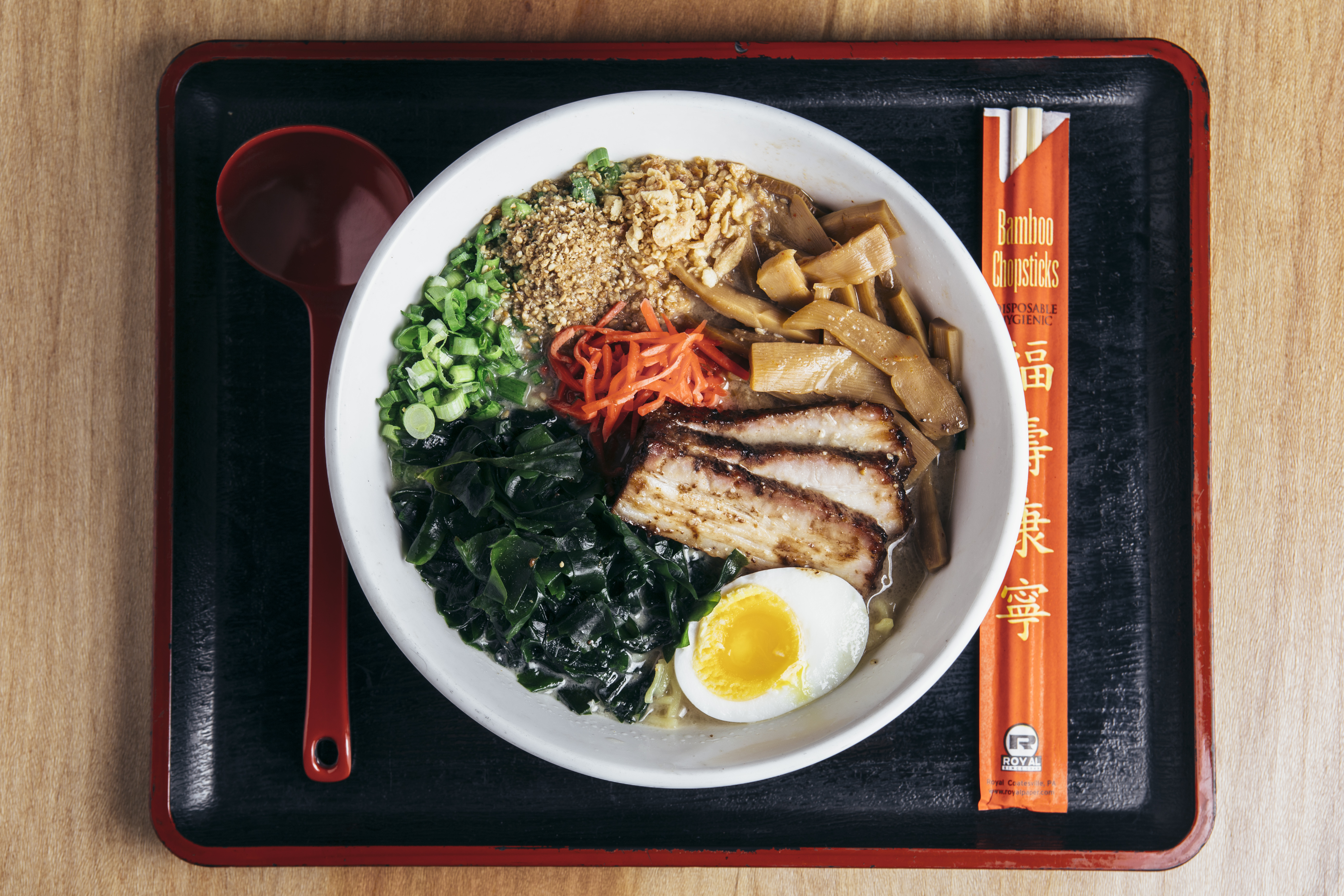 A white bowl filled with ramen noodles, soup, green vegetables, slices of pork, and a boiled egg sits on a black tray. A red soup spoon and chopsticks sit beside it.