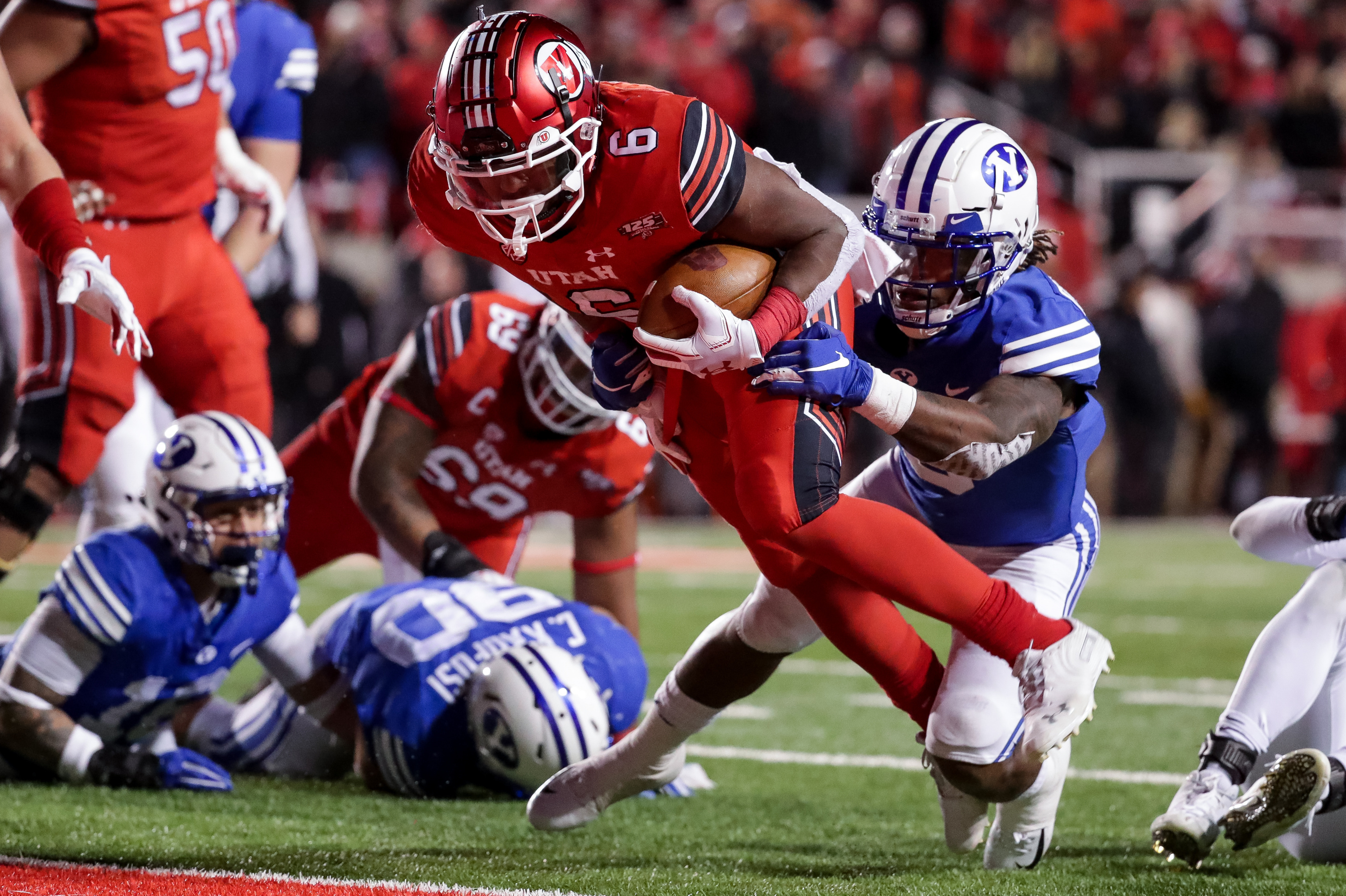 Utah Utes running back Armand Shyne (6) gets past Brigham Young Cougars defensive back Dayan Ghanwoloku (5) to run the ball in for the go-ahead touchdown, putting Utah up 28-27 over the Brigham Young Cougars at Rice-Eccles Stadium in Salt Lake City on Sat