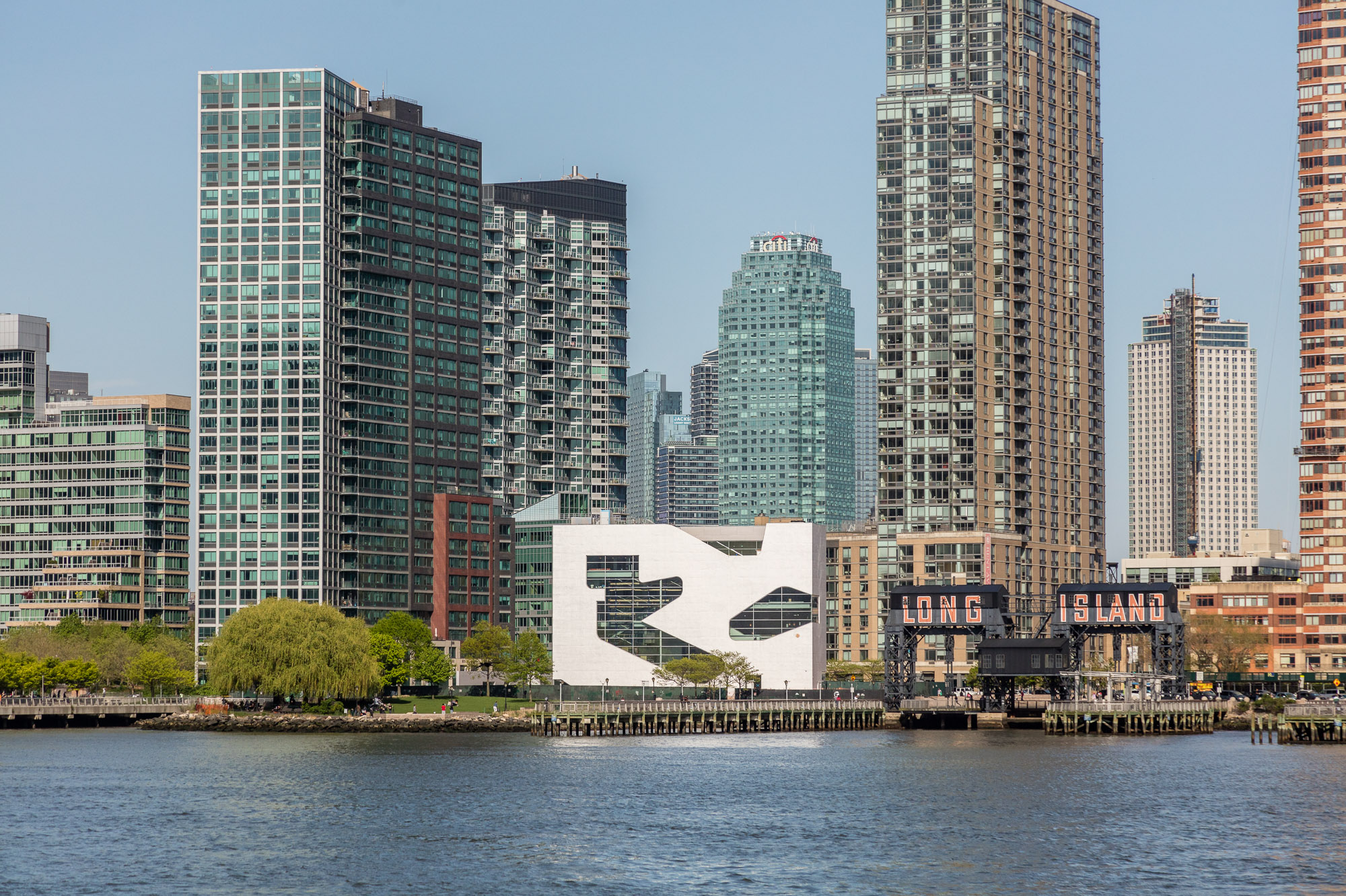 A small white building with cut-outs on its facade sits on a waterfront site. It is surrounded by tall glass buildings.