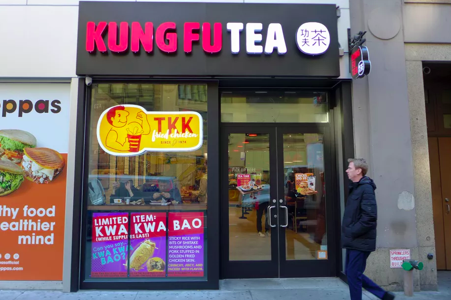 An exterior shot of a small New York City storefront, a combination TKK Fried Chicken and Kung Fu Tea location. A man in a winter coat walks by.