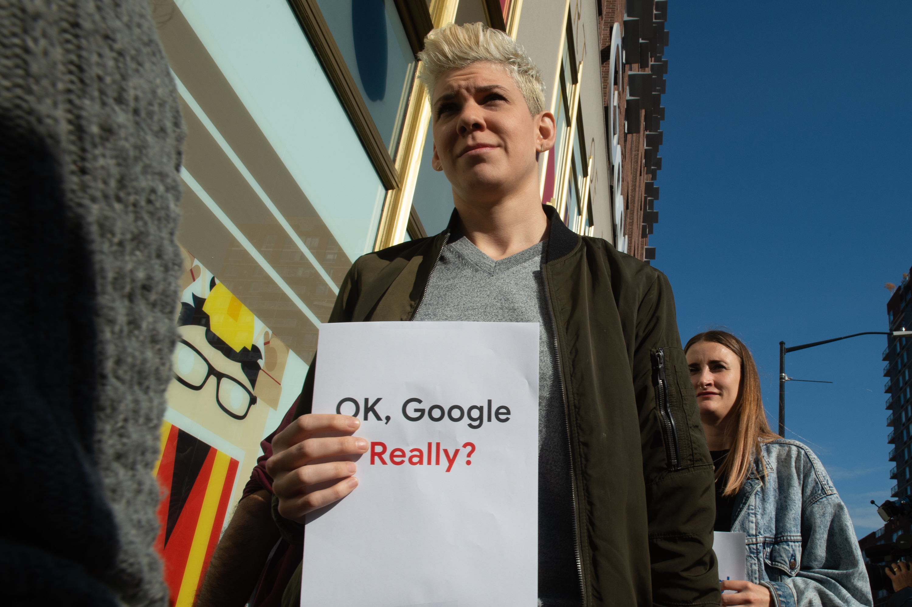 "Google employees protest outside the company's office in New York; one holds a sign that reads, ""Ok Google really?"""